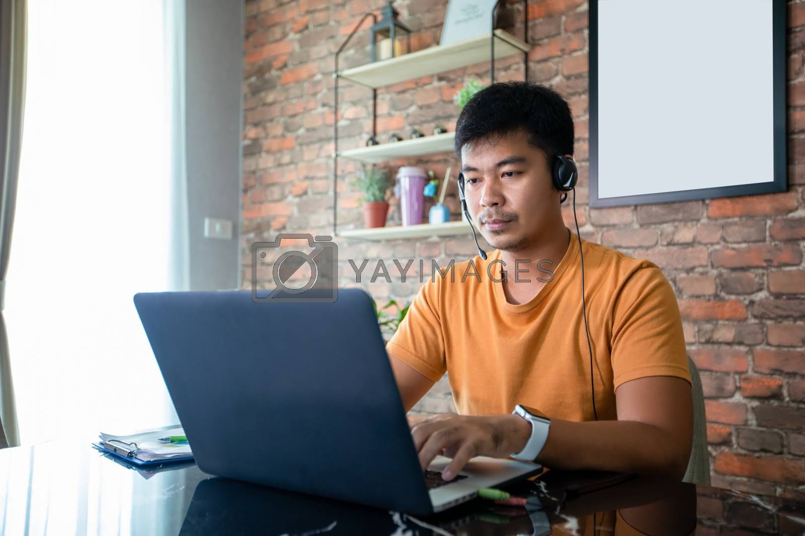 Asian businessmen is using notebook computers and wear headphones for online meetings and working from home.