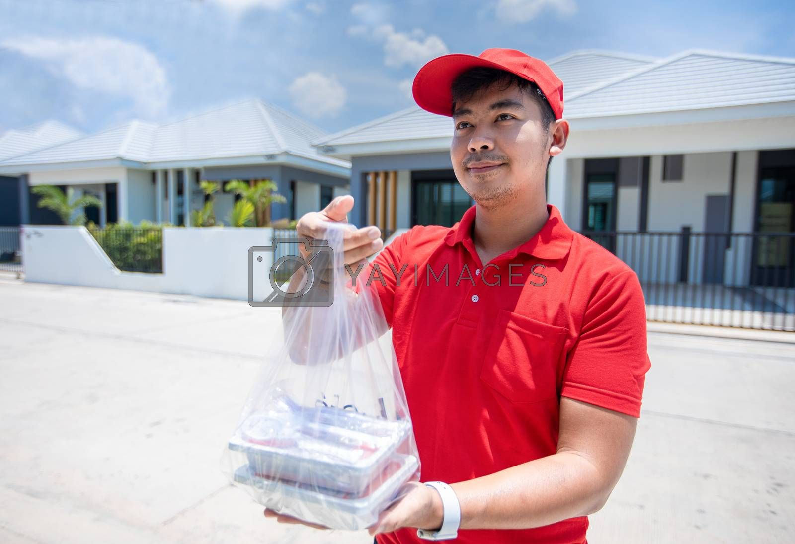 Asian delivery servicemen wearing a red uniform with a red cap and handling food boxes in plastic bags to give to the customer in front of the house. Online shopping and Express delivery