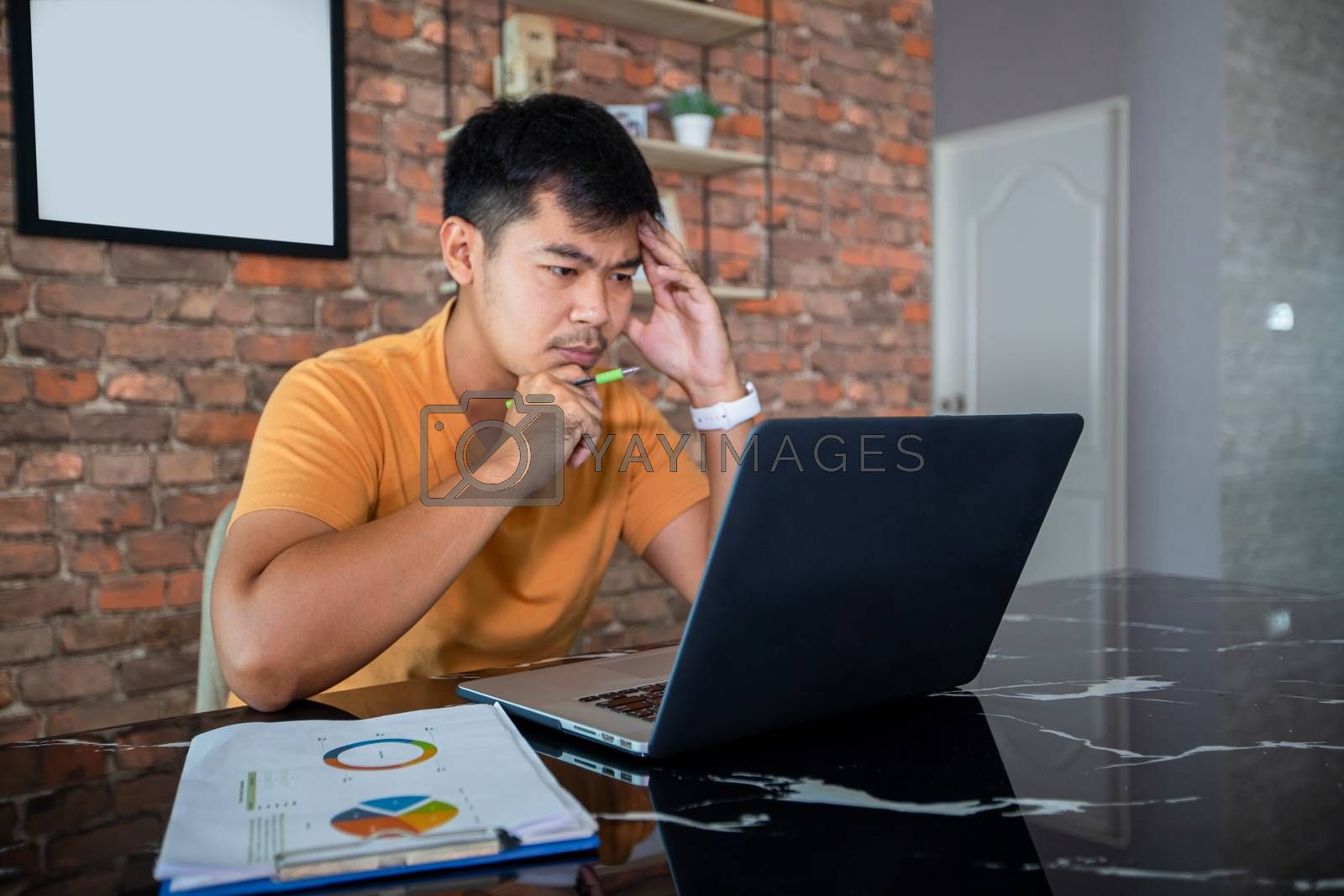 Asian man uses a notebook computer and works hard and meeting at home and he is stressed and Headache.