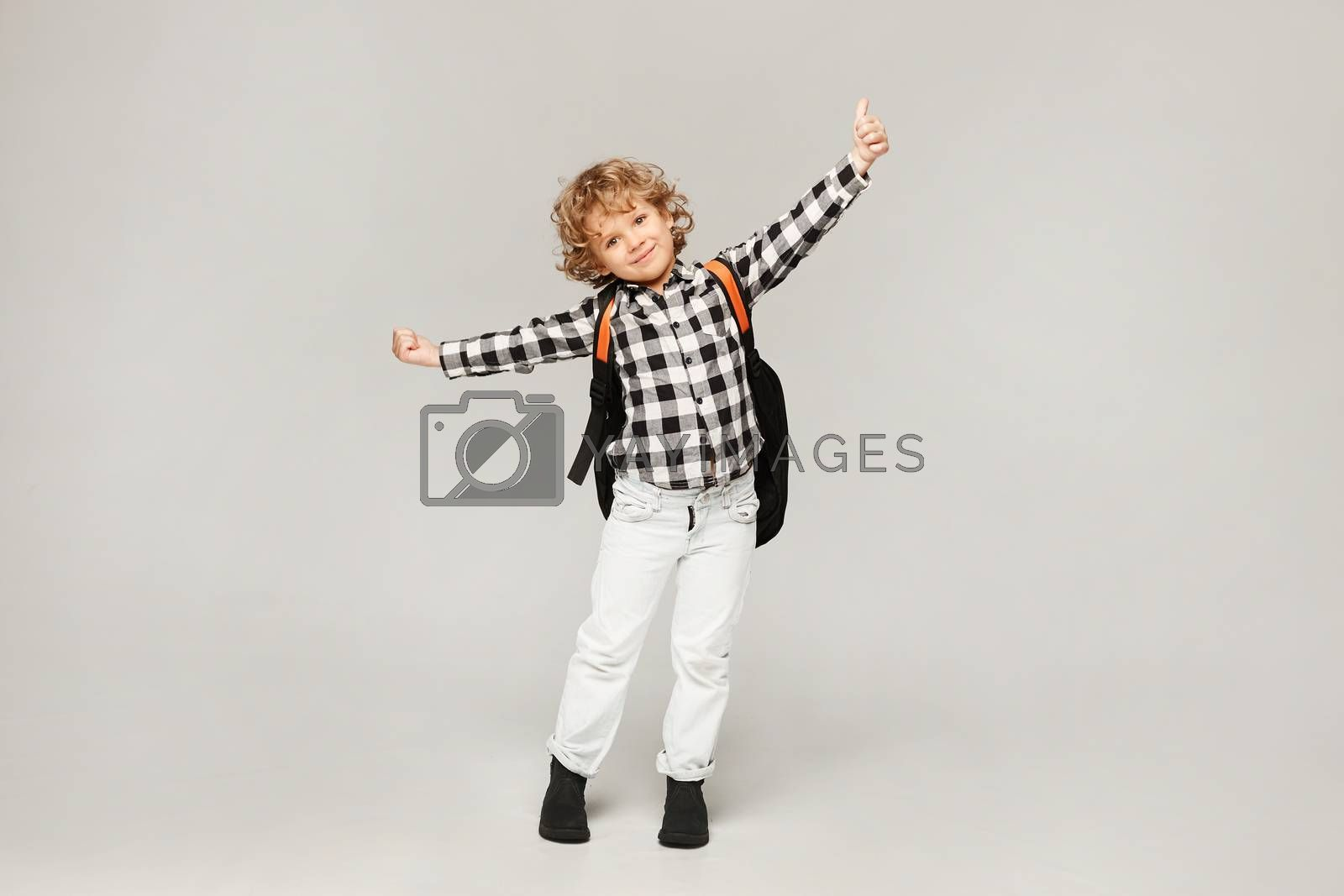 A little schoolboy is happy to start the school year. Happy kid with a backpack posing at the white background, isolated. by Ina