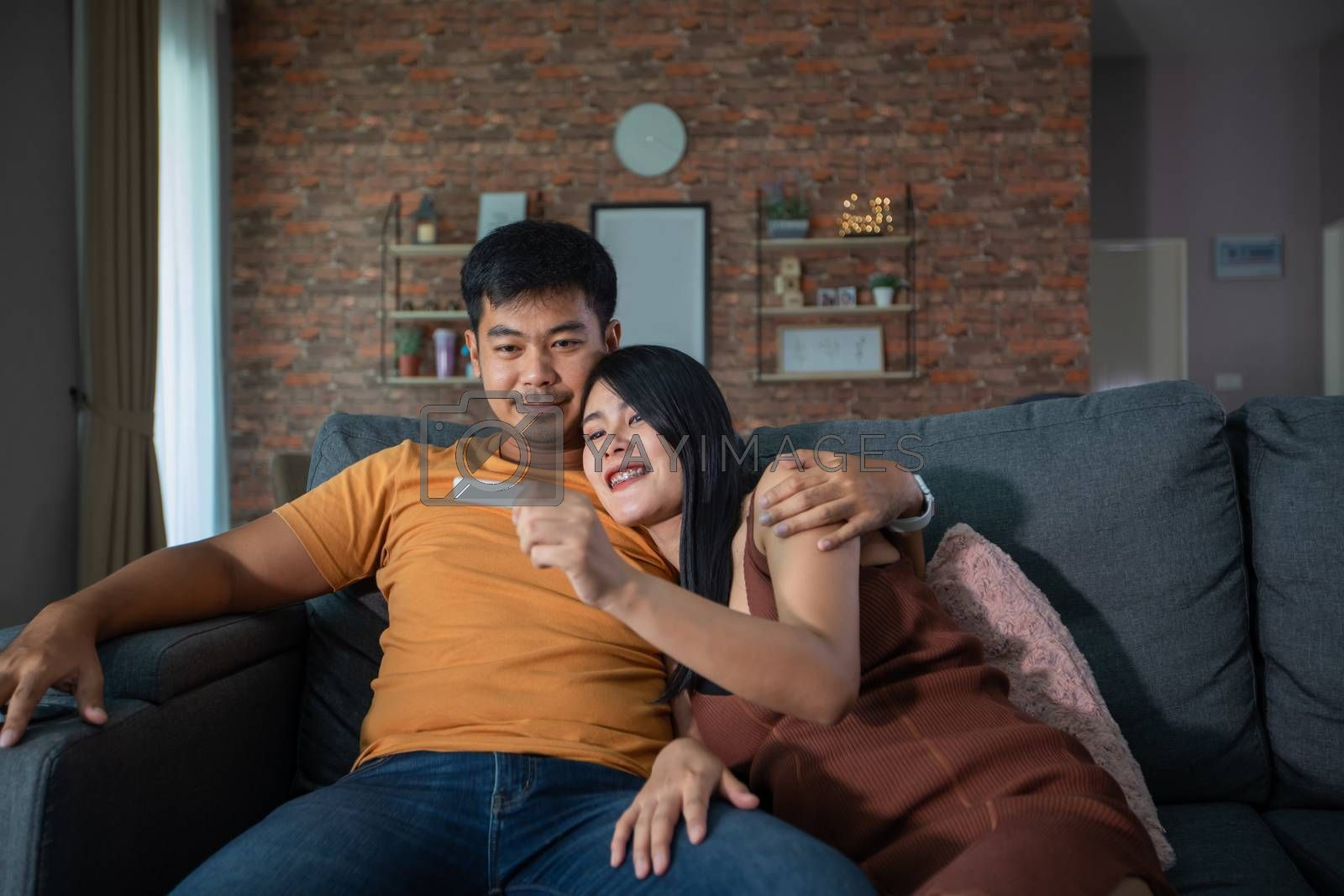 Happy Asian couple smiling looking cheerful after a home pregnancy test in sofa at home by Tuiphotoengineer