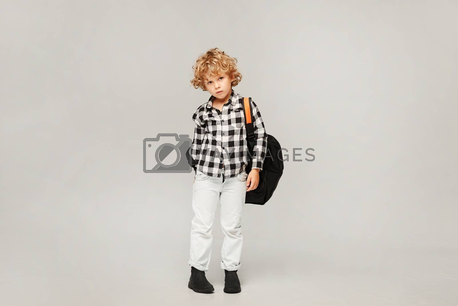 Sad little schoolboy in shirt and jeans with backpack isolated over white background. Back to school.