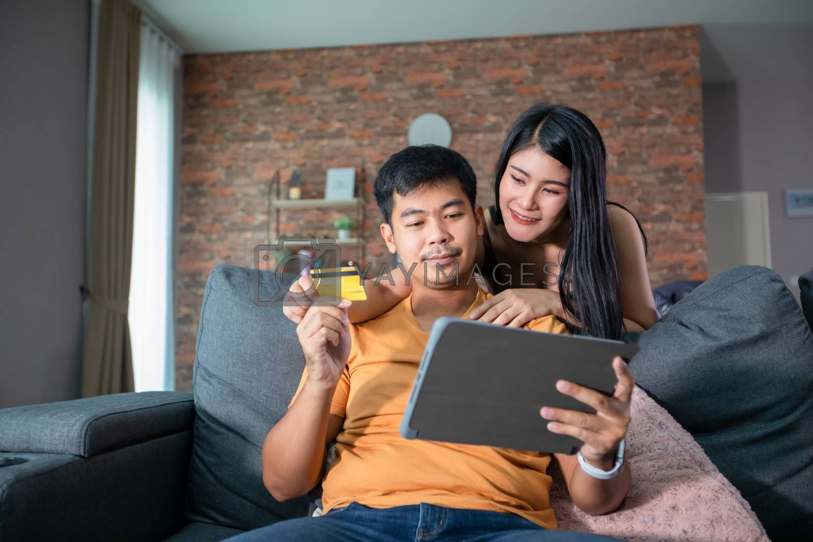 Asian Couple shopping online and paying with credit card at laptop computer,Happy couple at home surfing the net on sofa