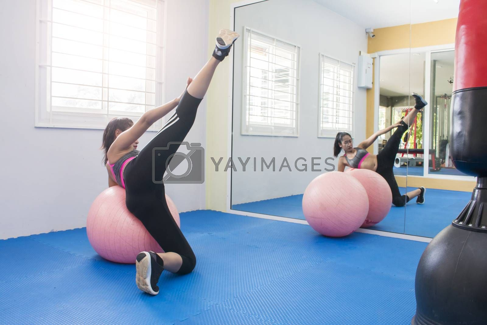 attractive young woman working out in front of mirror in fitness club,Woman Doing Yoga Exercises In Gym