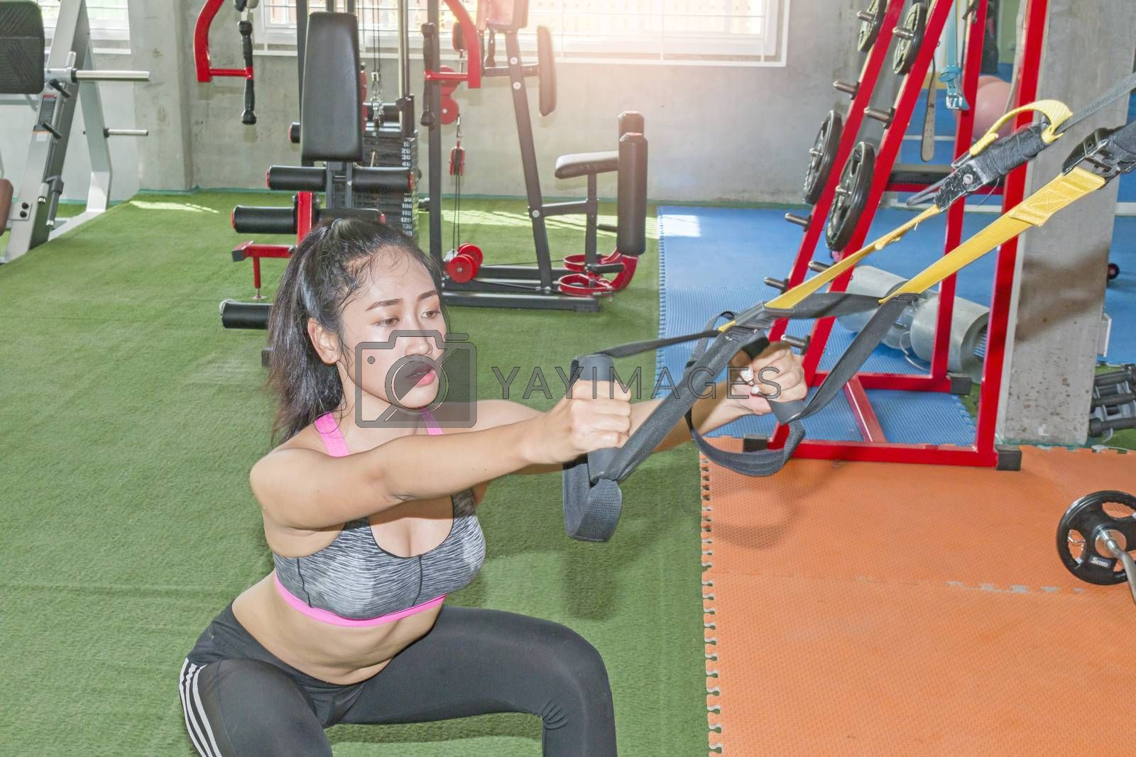 Fitness trx suspension straps training exercises women , working with own weith at gym