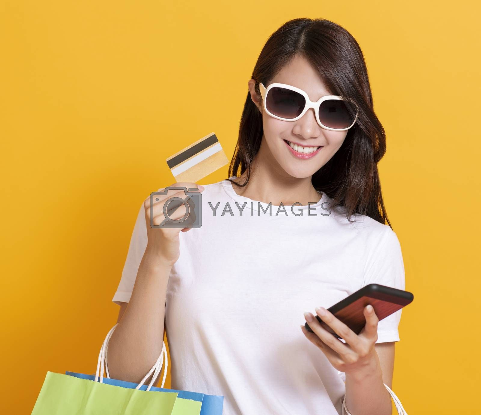 happy young woman in summer dress and using mobile phone shopping online with credit card