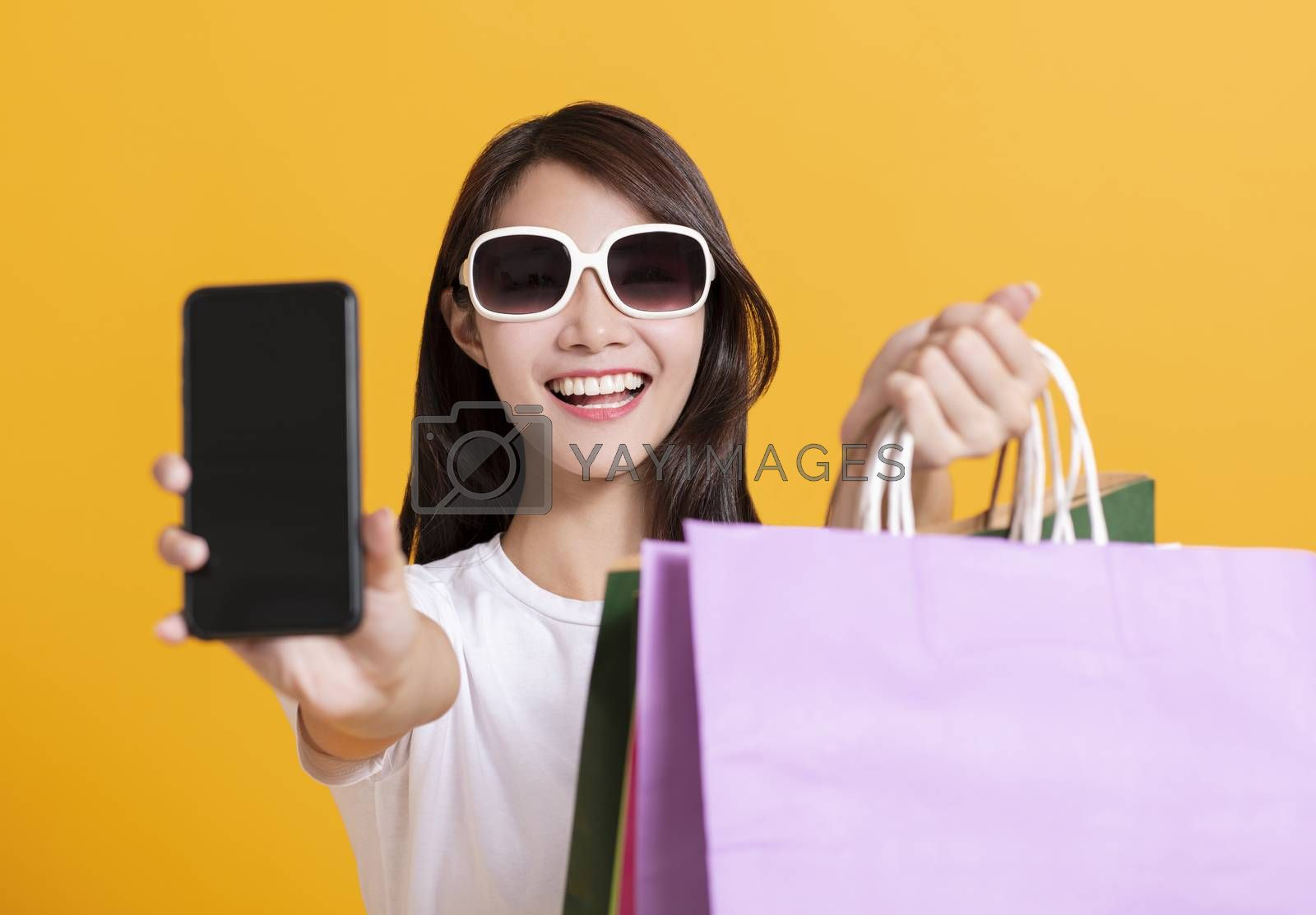 happy young woman showing mobile phone and shopping bags