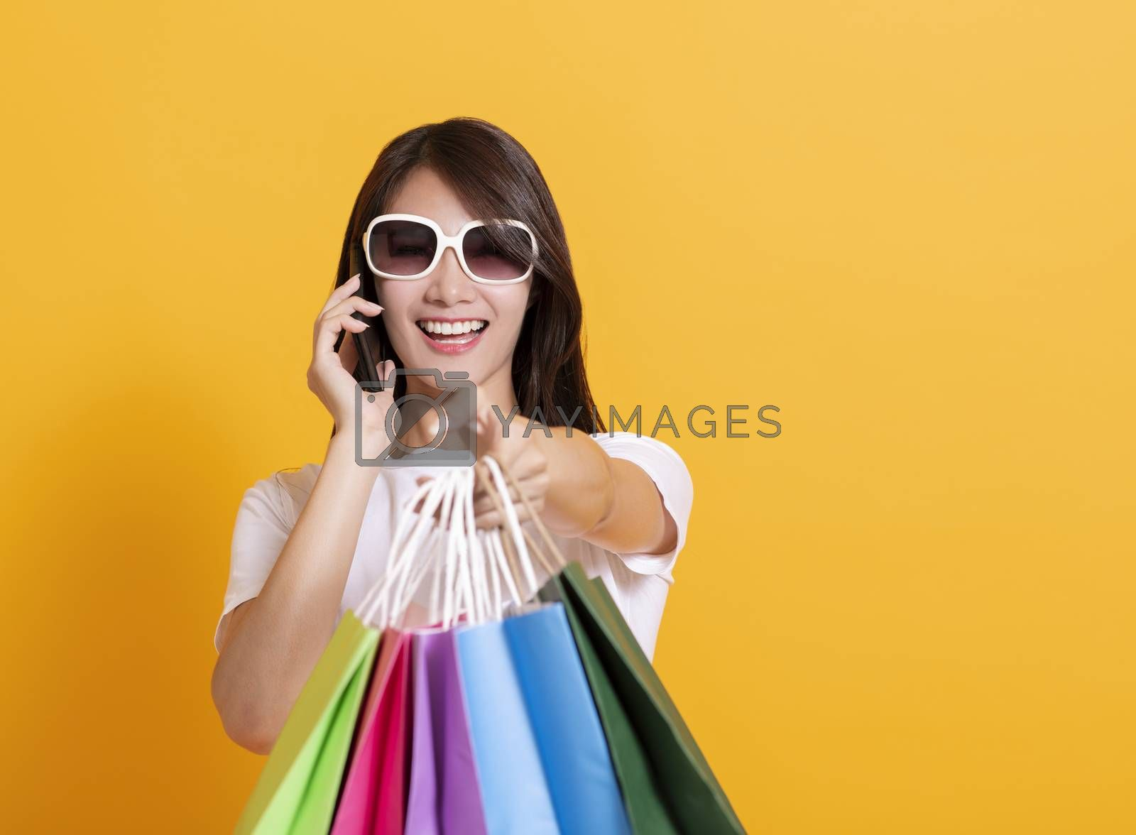 happy young woman showing  shopping bags and talking on the phone