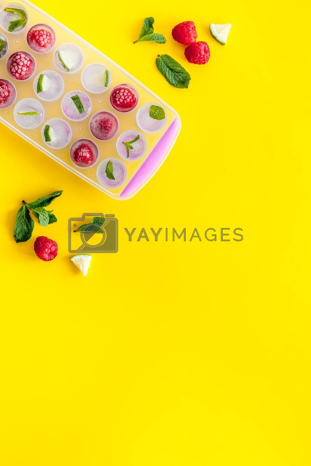Ice tray with berries, lime and mint on background top view copy space.