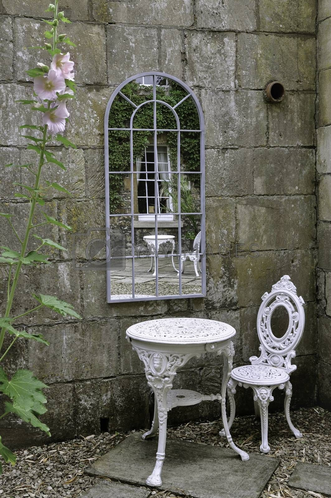 An English courtyard country garden, with white wrought iron table and chair against a Georgian style window