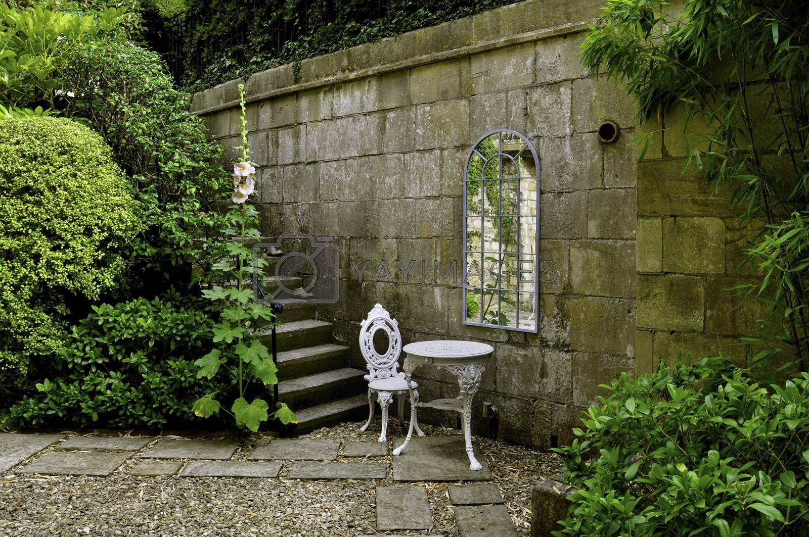 A courtyard country garden with stone walls, steps and flagged paths. With white wrought iron patio furniture, a Georgian style mirror and lush trees, shrubs and hollyhocks.
