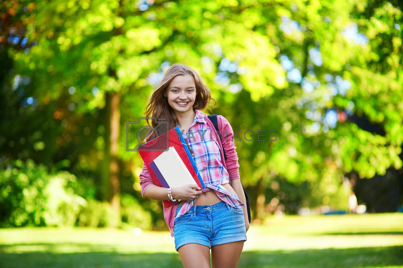 Young student girl outdoors going back to school and smiling