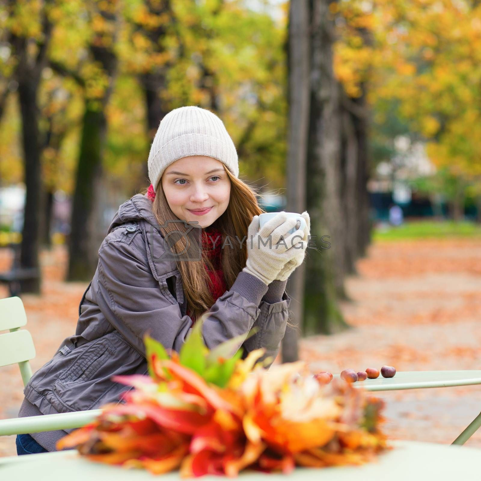 Girl drinking coffee or tea outdoors on a fall day