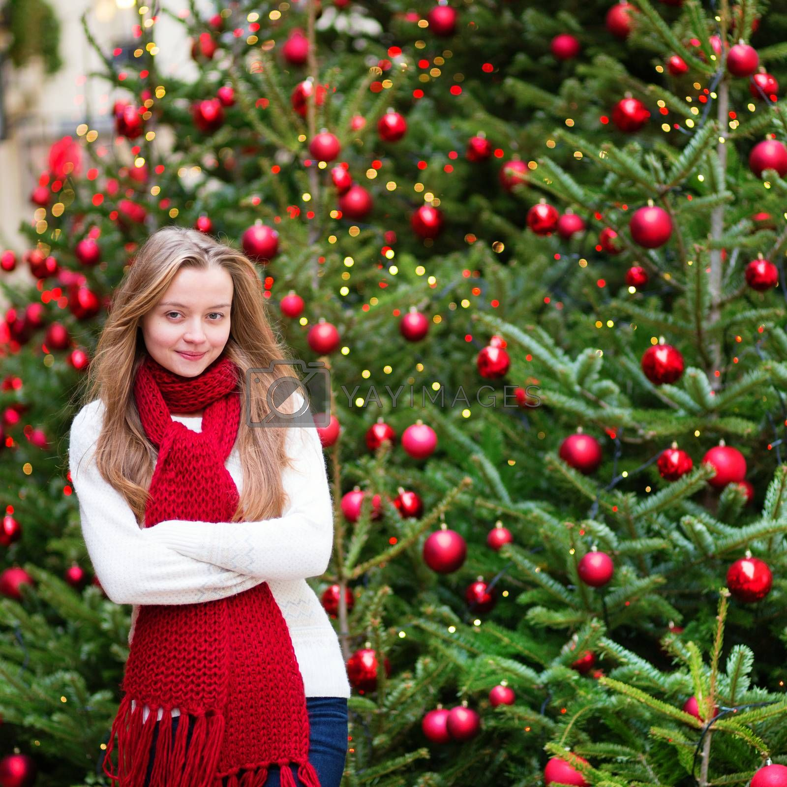 Girl with a brightly decorated Christmas tree