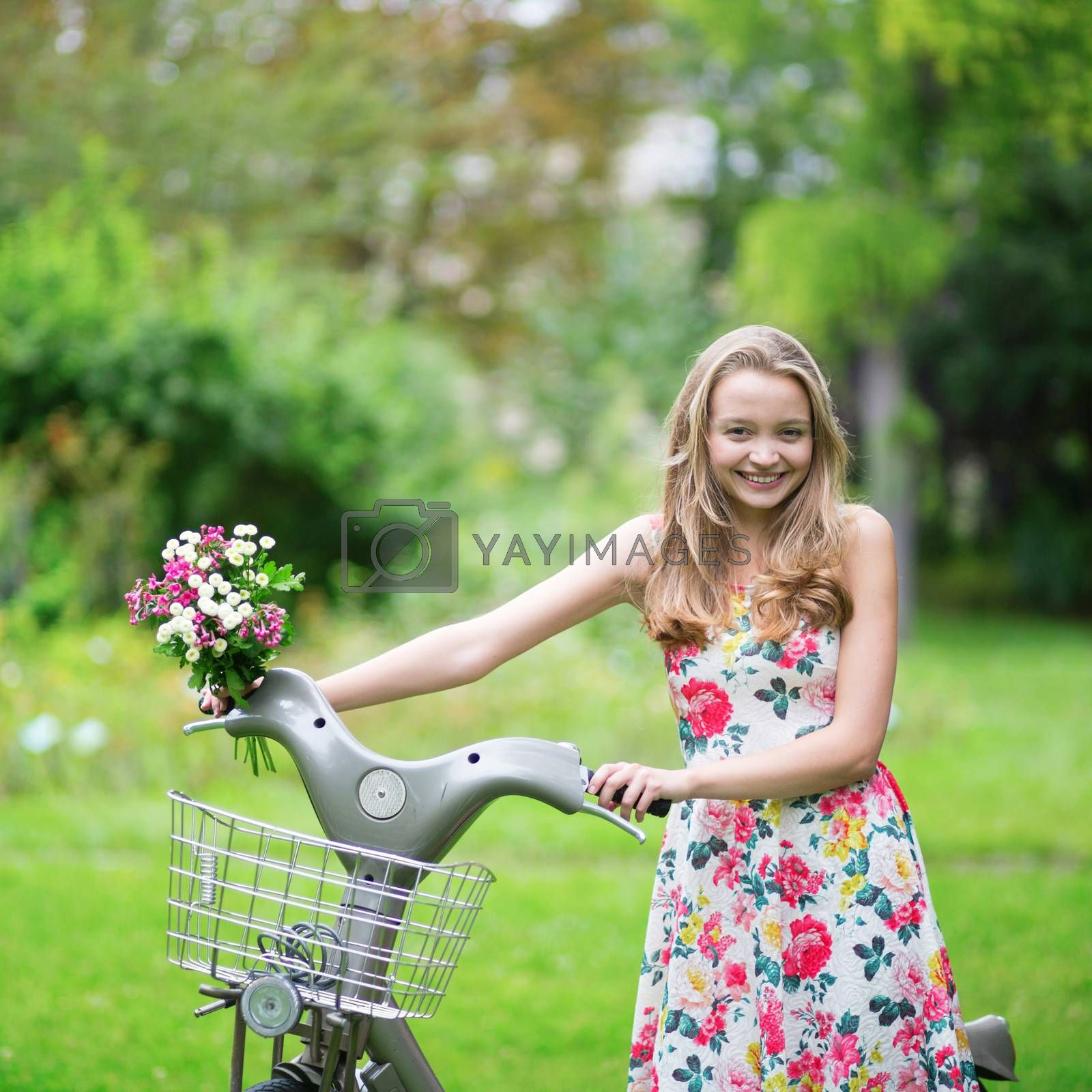 Beautiful young girl with bicycle in the countryside