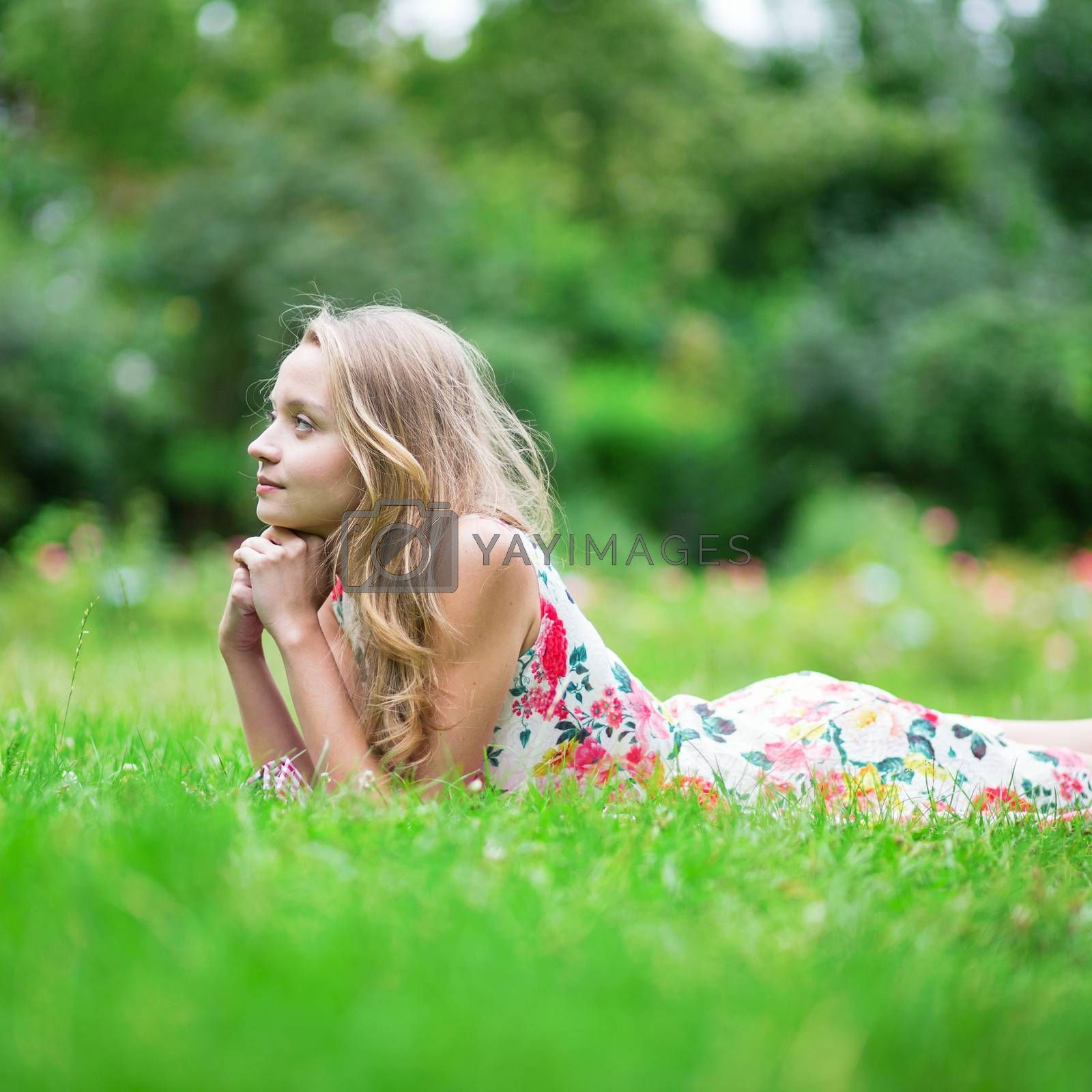Beautiful young girl lying on the grass and enjoying summer day