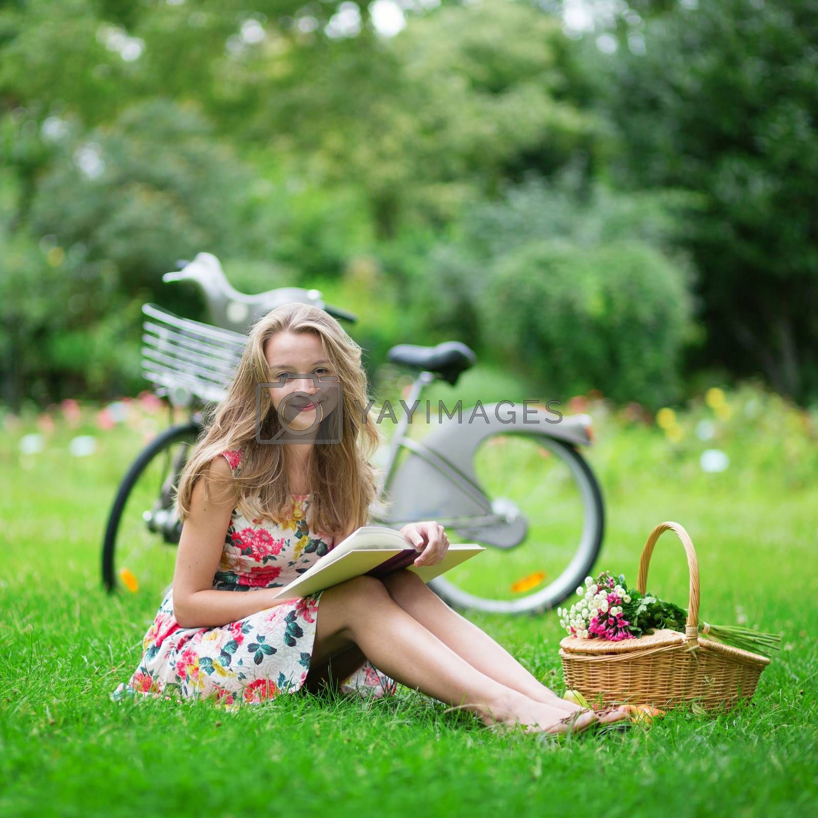 Beautiful young girl with bicycle in the countryside, reading a book