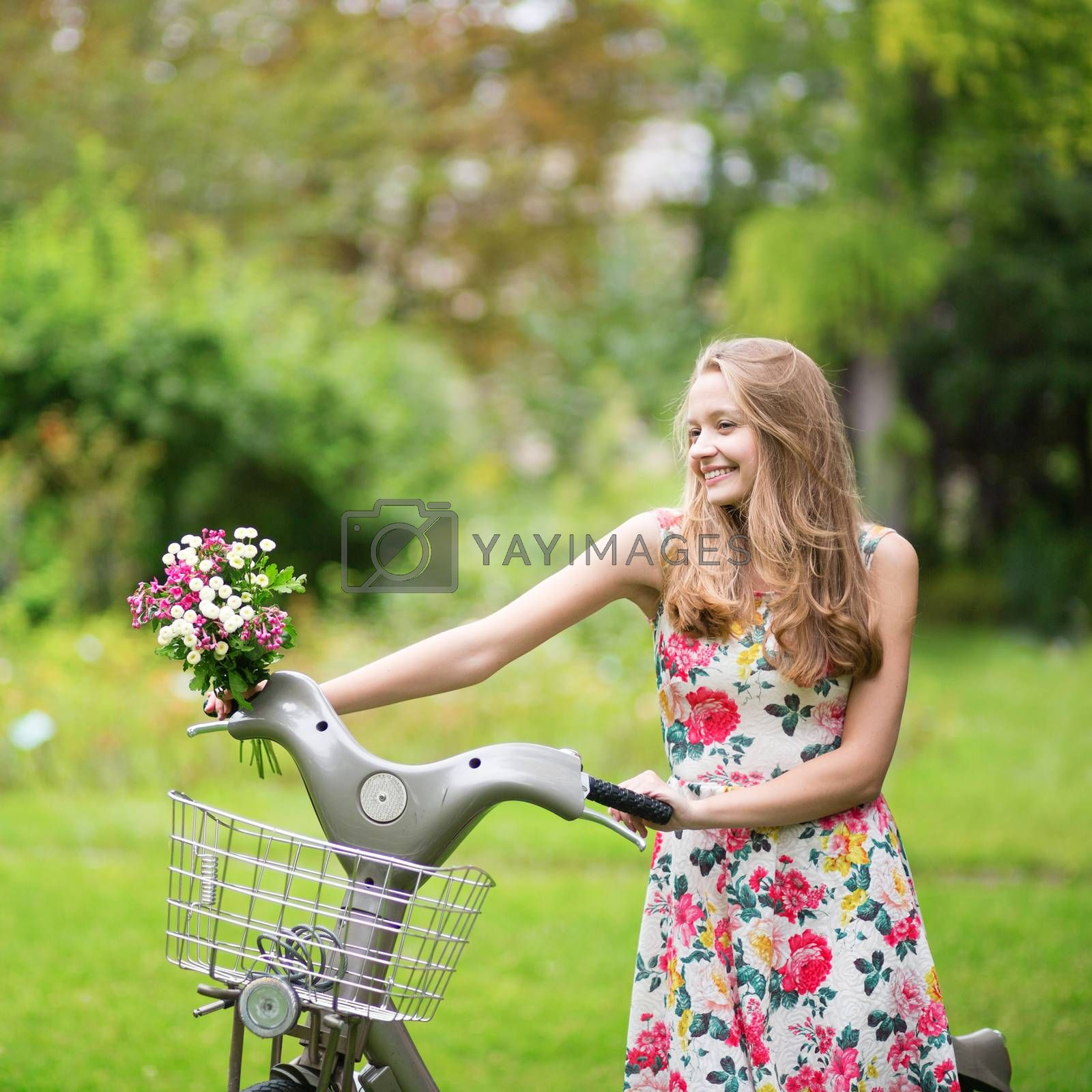 Happy young girl with bicycle in park on a summer day