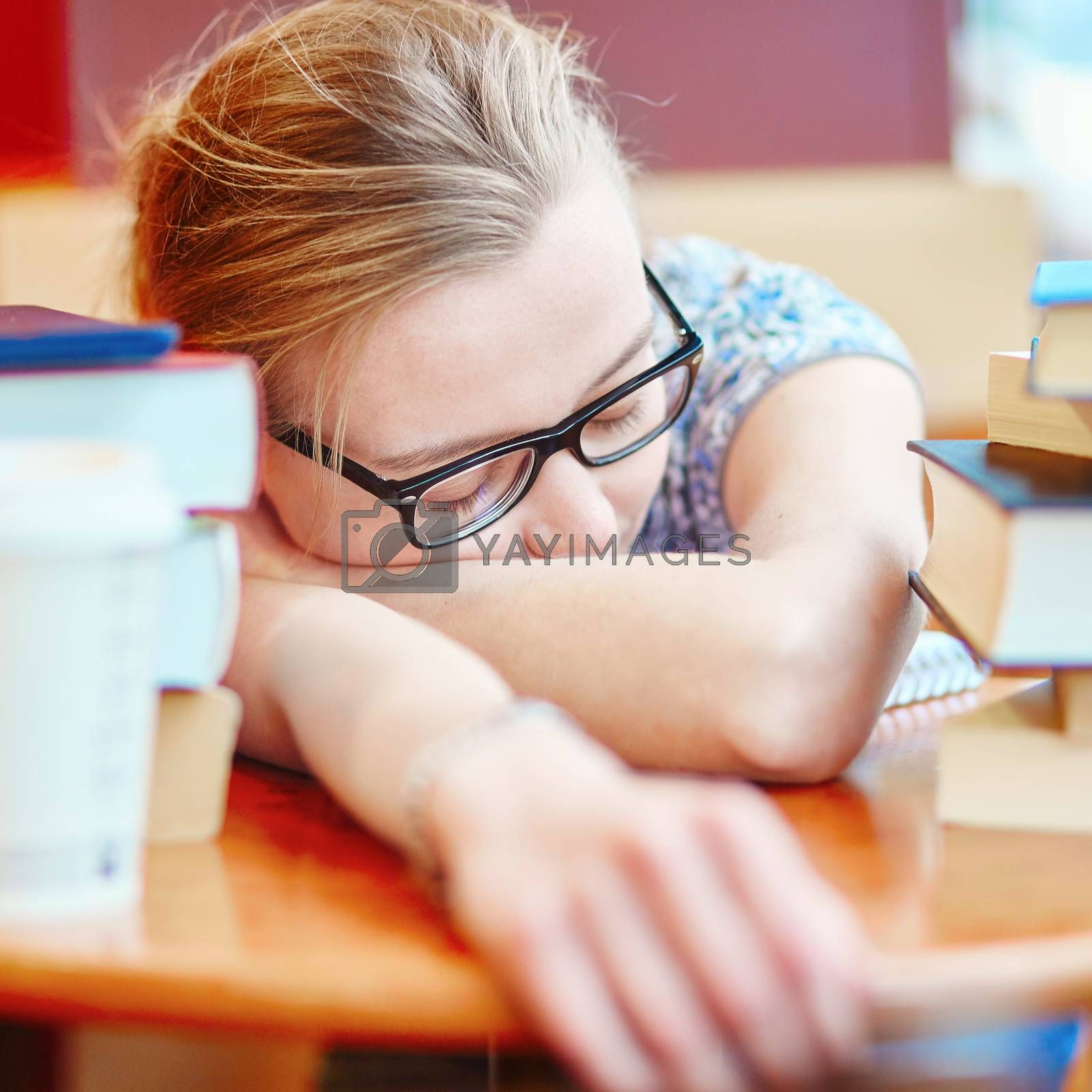 Beautiful young student with lots of books, sleeping on the table, tired of preparing for exams. Shallow DOF