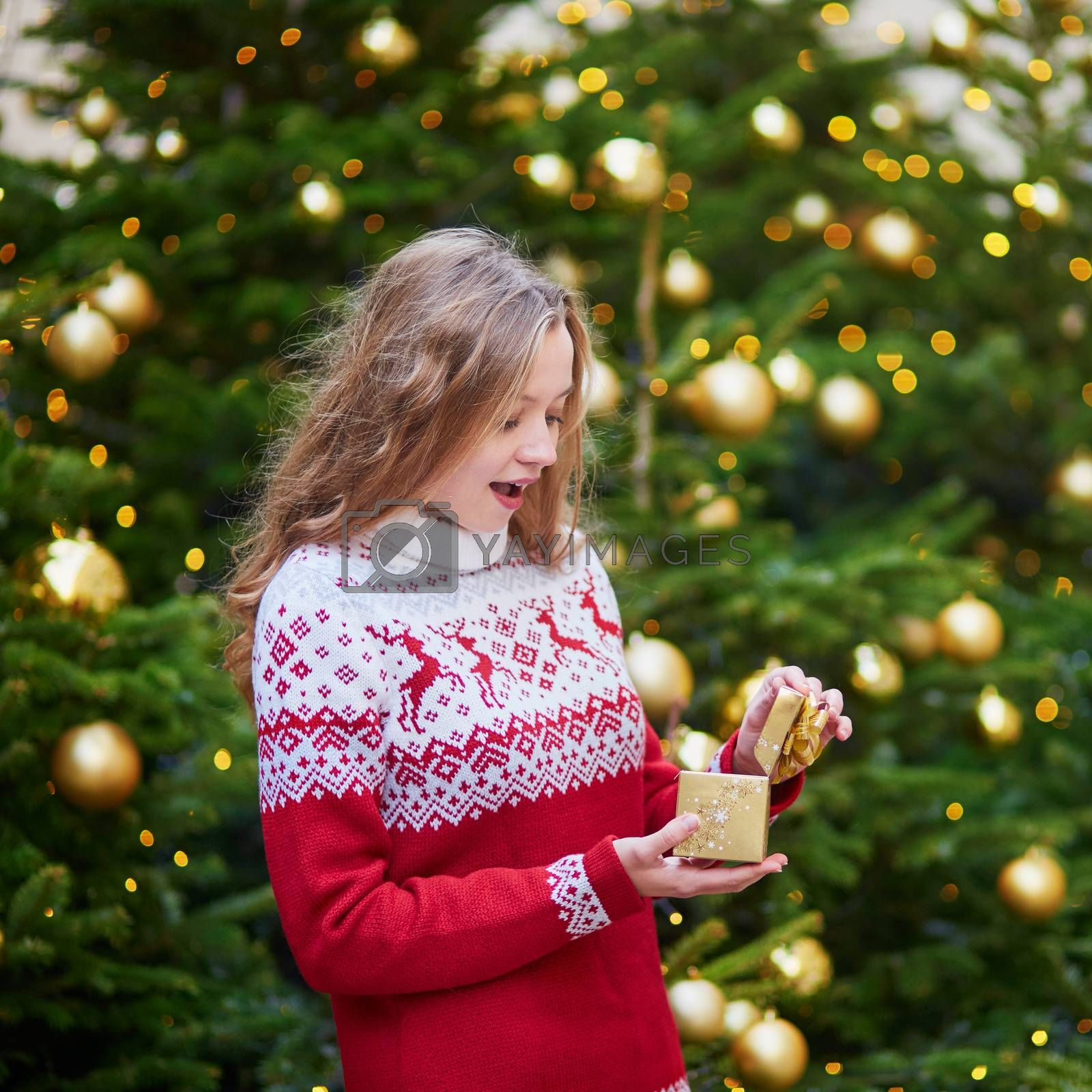 Cheerful girl with Christmas present near decorated Christmas tree