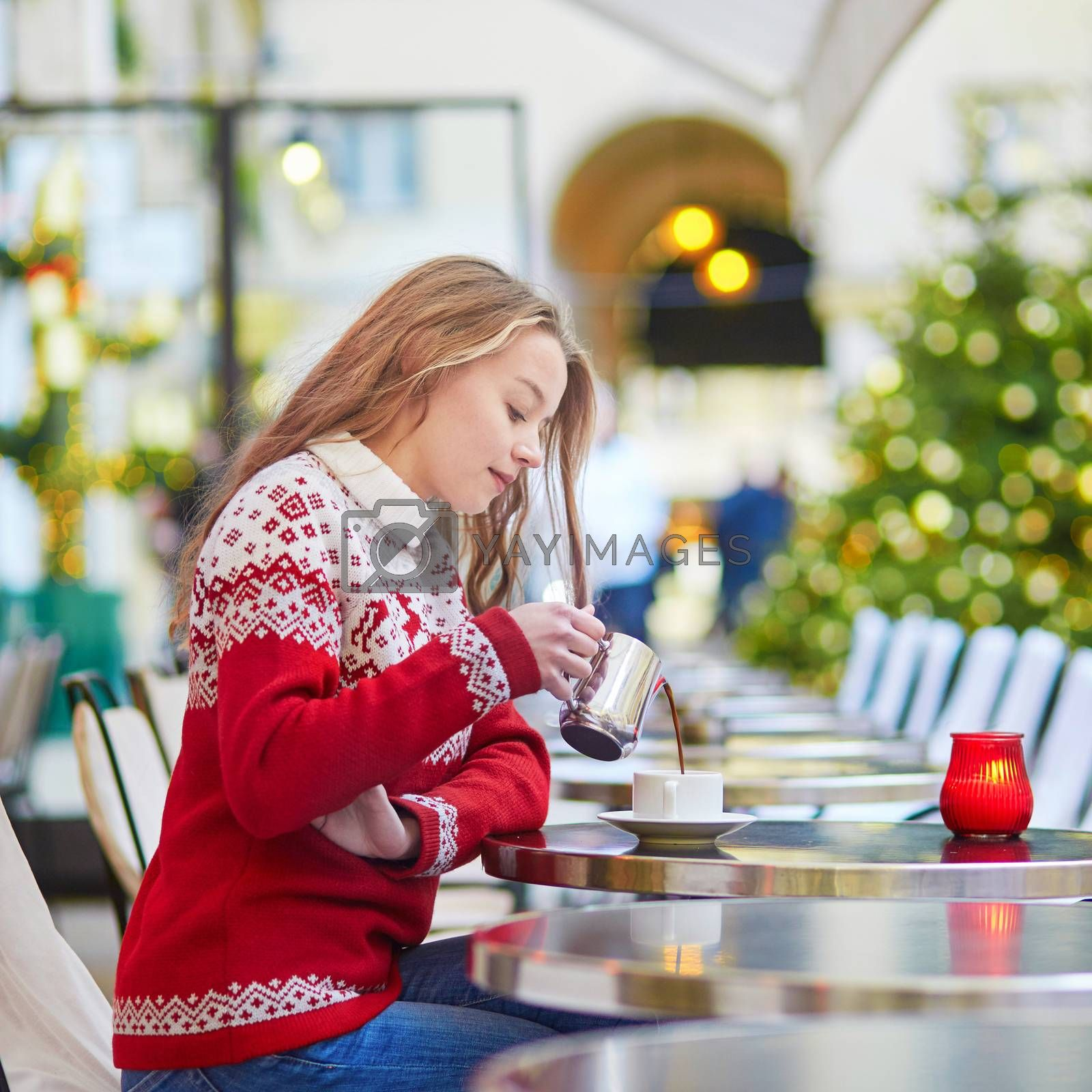 Cheerful young woman drinking hot chocolate in a cozy outdoor Parisian cafe decorated for Christmas