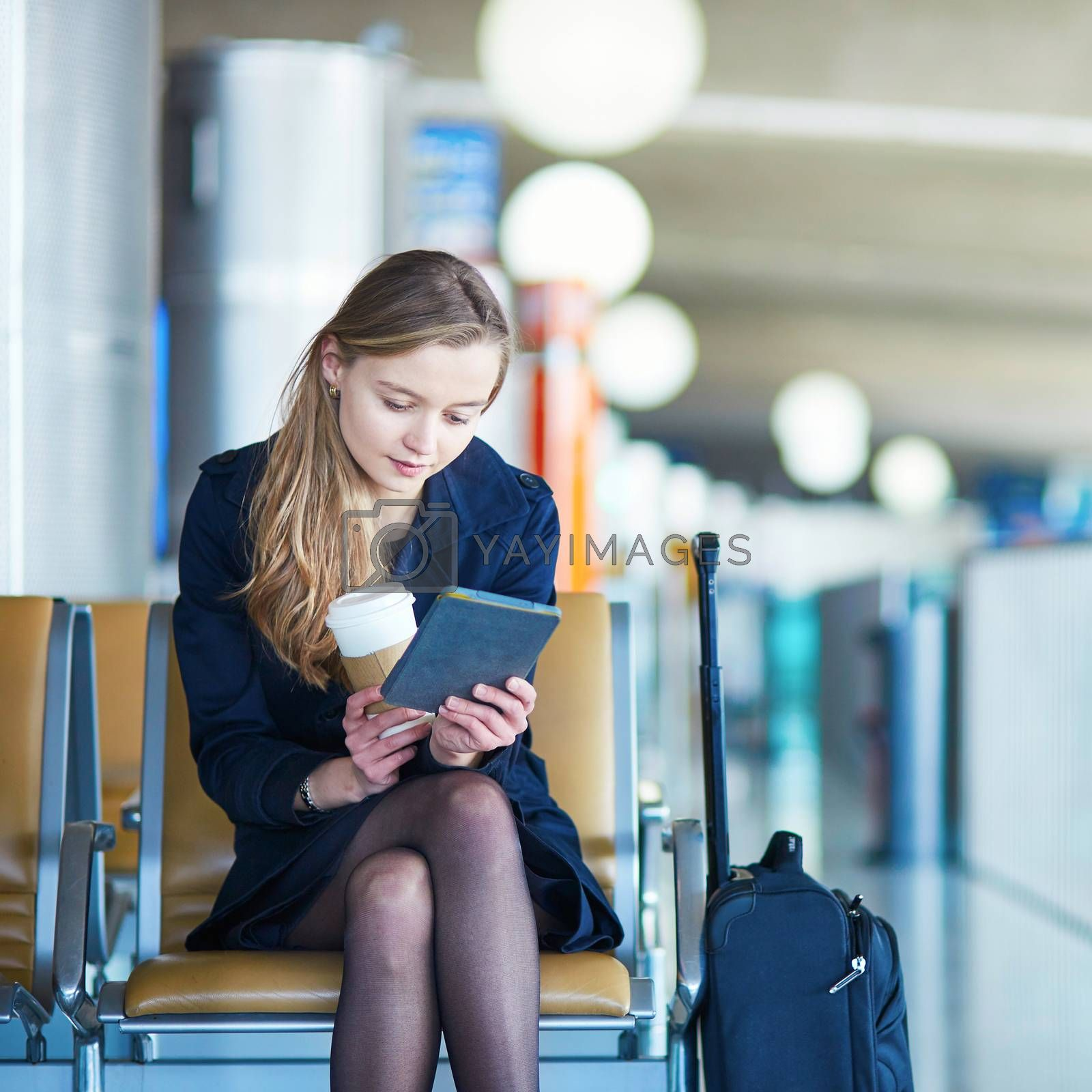 Young woman in international airport reading a book while waiting for her flight