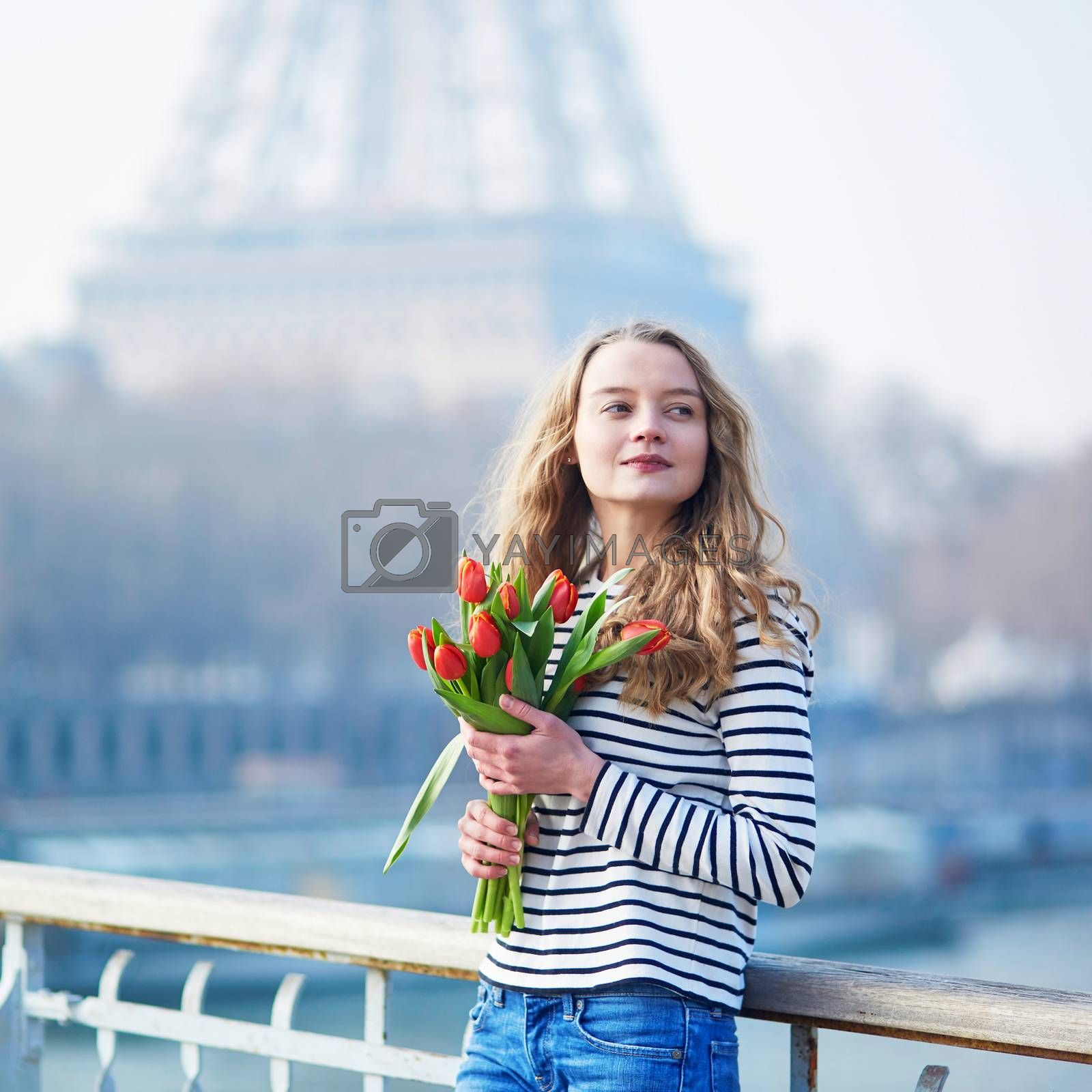 Beautiful young girl with bunch of red tulips near the Eiffel tower in Paris, France on a clear spring day