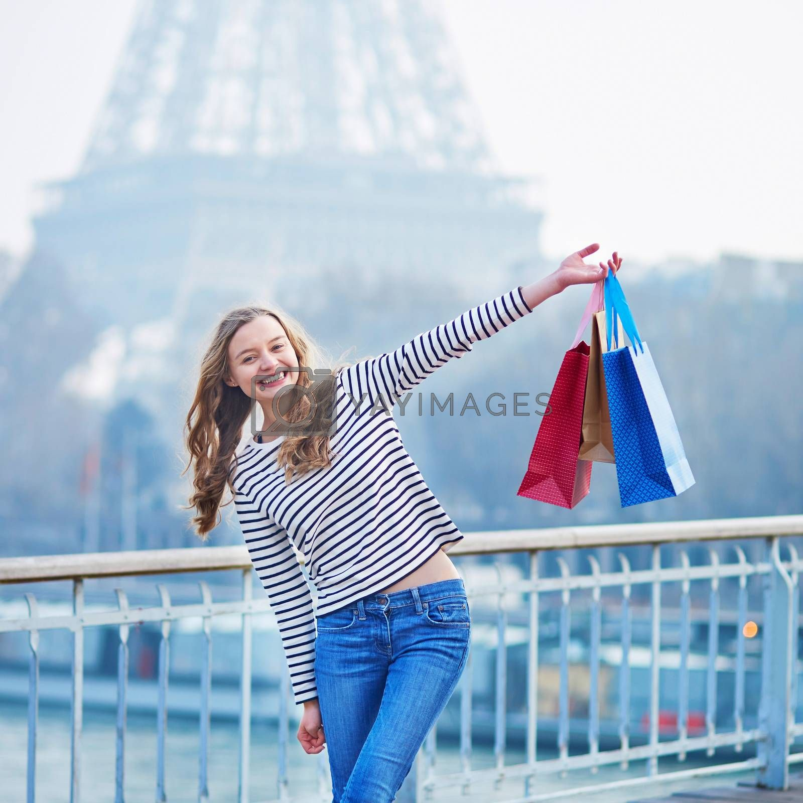 Cheerful young French girl with shopping bags near the Eiffel tower in Paris. Tourism and shopping in France concept