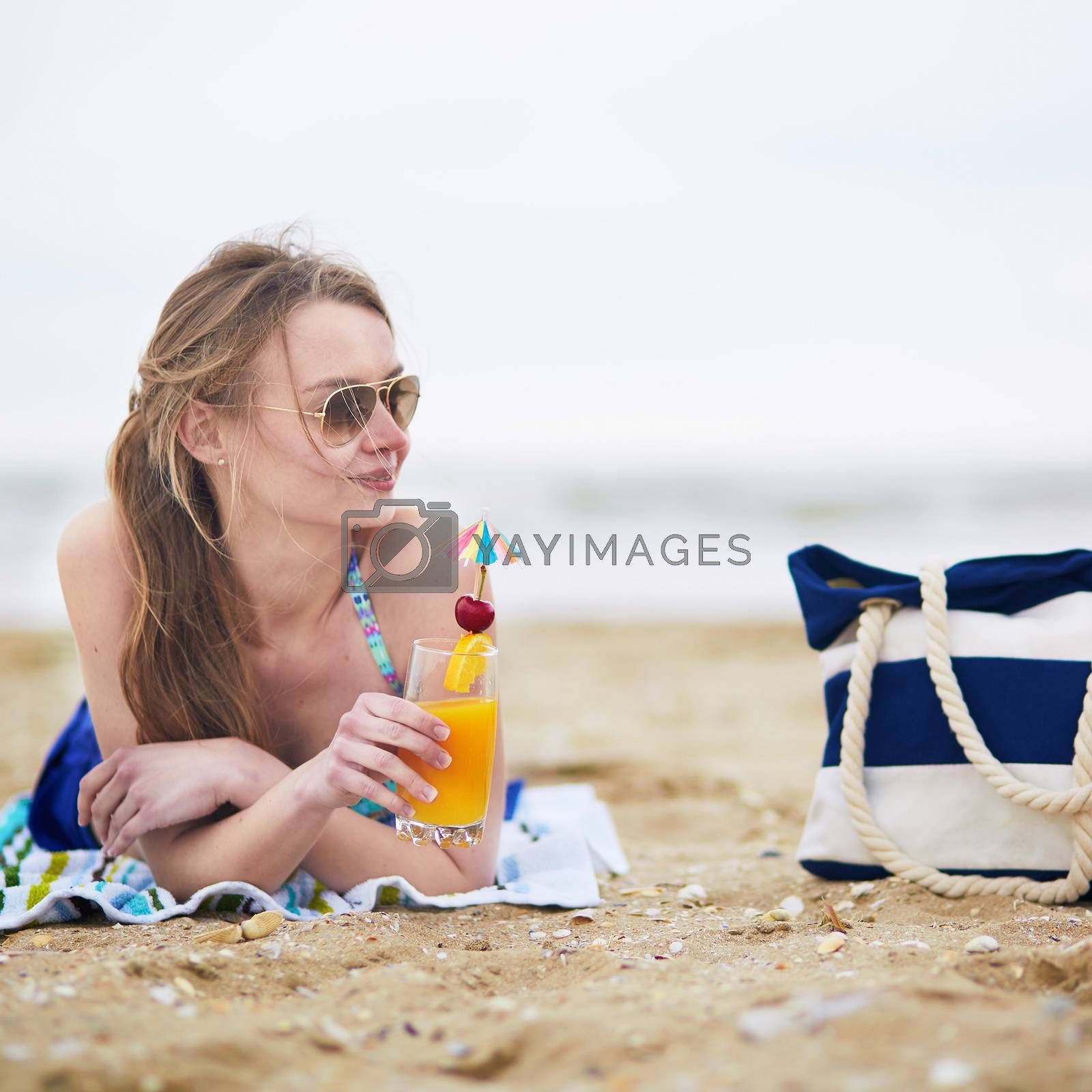 Beautiful young woman relaxing and sunbathing on beach, drinking delicious fruit or alcohol cocktail with paper umbrella, beach bag on sand near the model