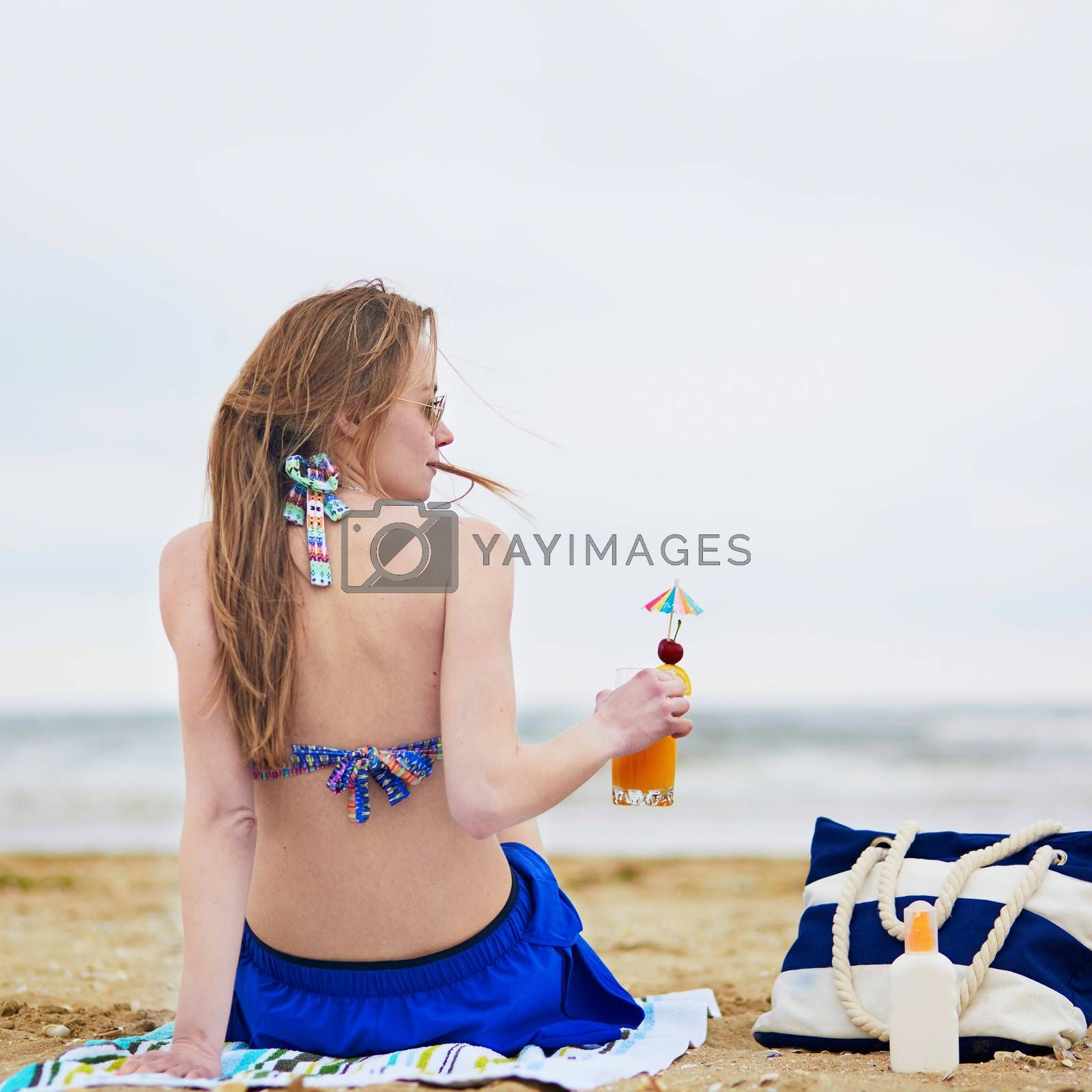 Beautiful young woman relaxing and sunbathing on beach, drinking delicious fruit or alcohol cocktail with paper umbrella, beach bag and sunscreen bottle on sand near the model
