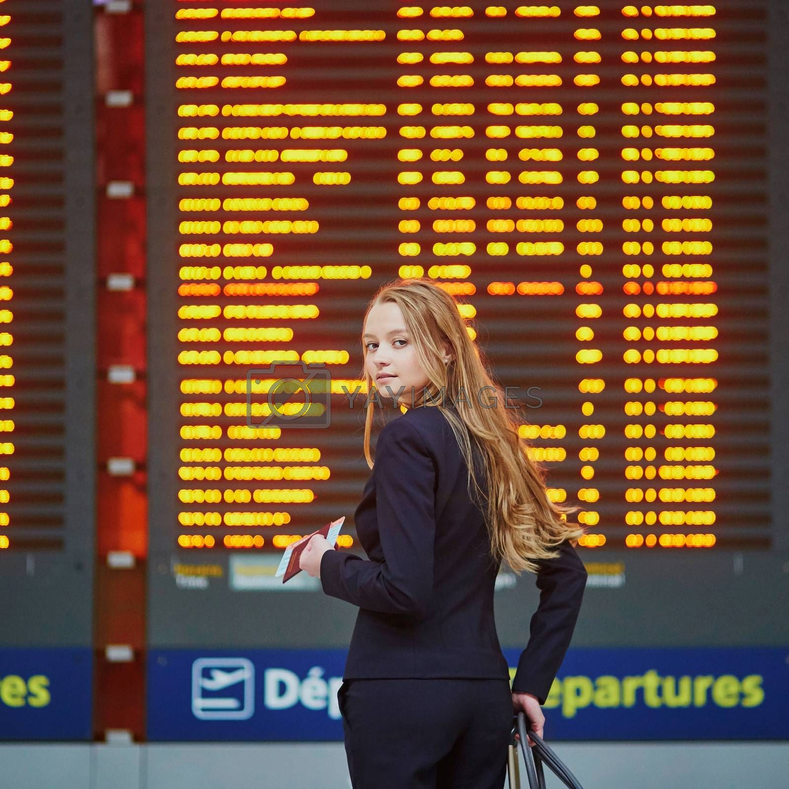 Young woman in international airport near large information display