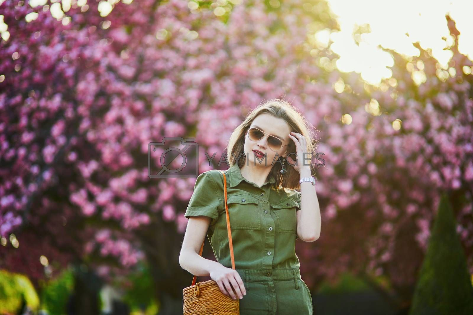 Beautiful French woman walking in Paris on a spring day at cherry blossom season