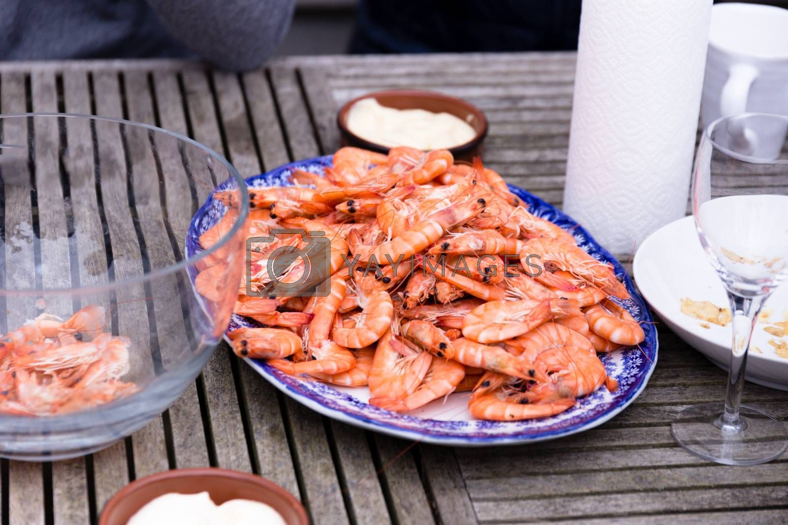 Friends aharing a plate of prawns at a social gathering