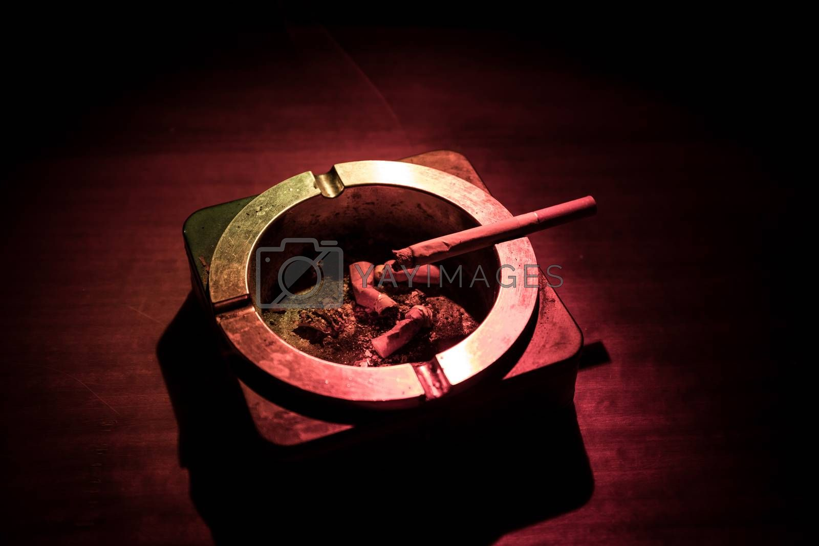 No smoking concept. Creative artwork table decoration with cigarettes. Cigarettes cause cancer and kill. Cigarette on ashtray on wooden table