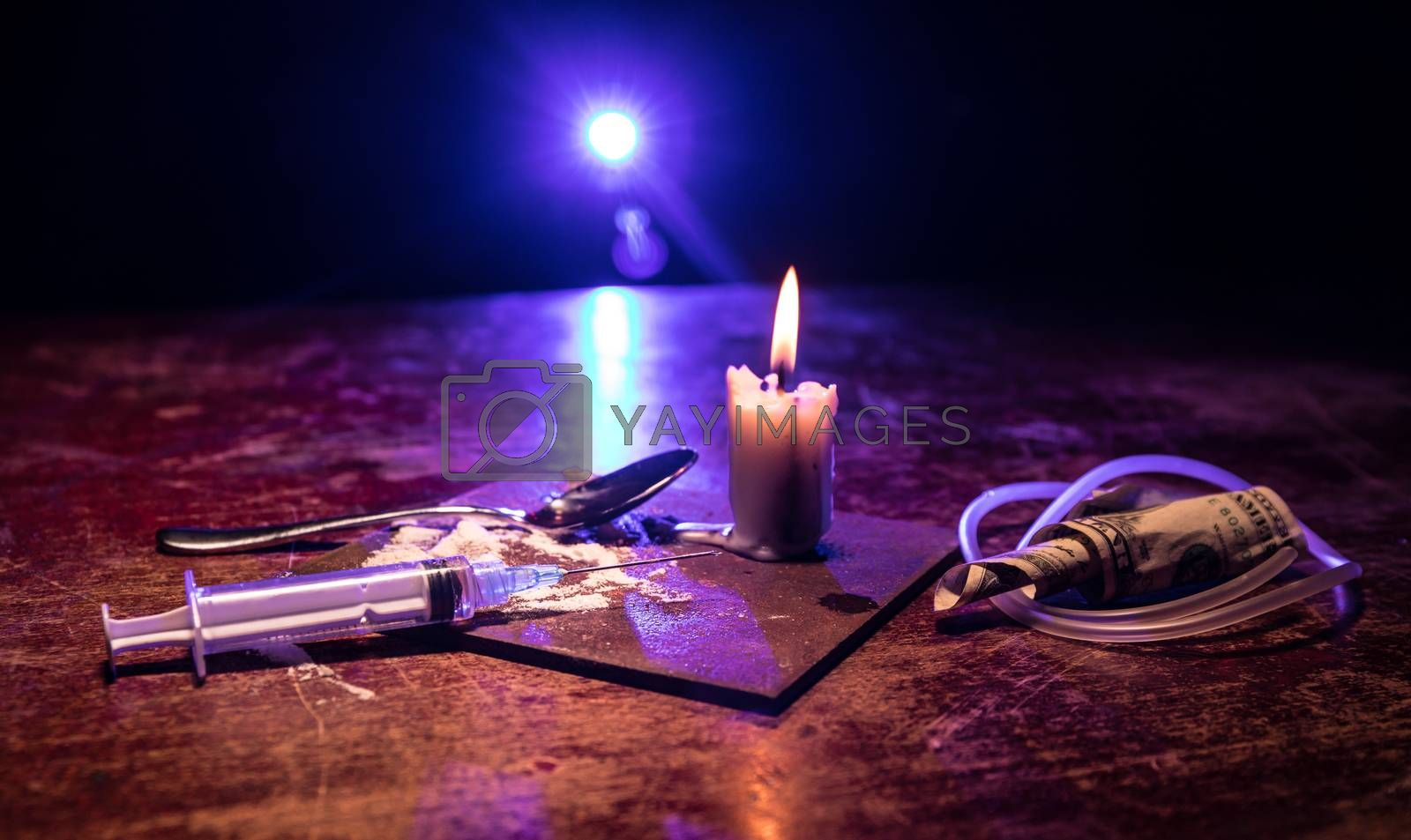 Narcotic drug problem concept. Drug syringe and narcotic attributes on wooden table. Purchase, possession and sale of drugs is punishable by law. Creative artwork decoration