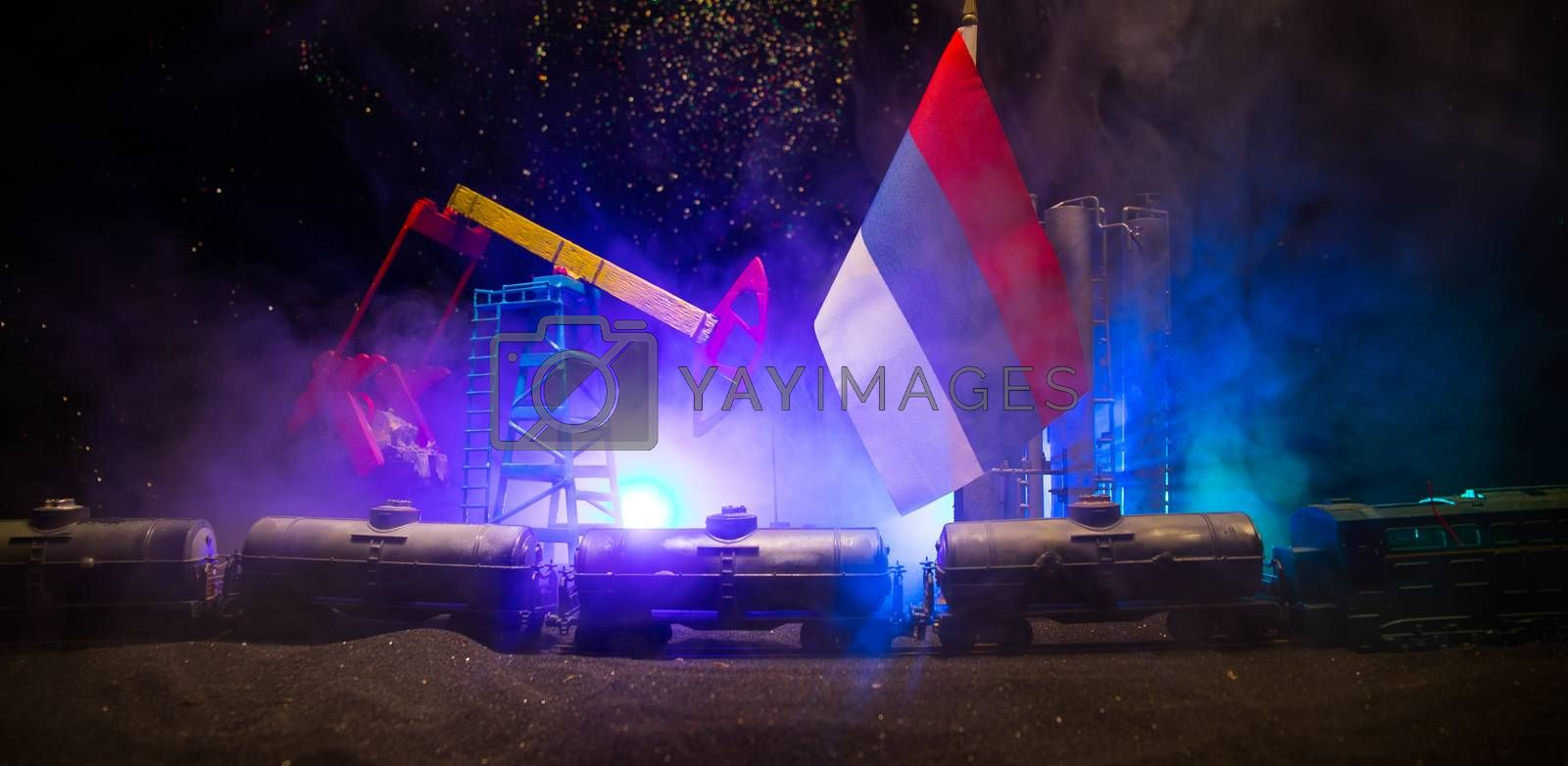 Business dialogue, oil agreement concept: National flags with Oil pump and oil refining factory at night. Night industrial railway with oil tank wagons. Selective focus. Artwork decoration.