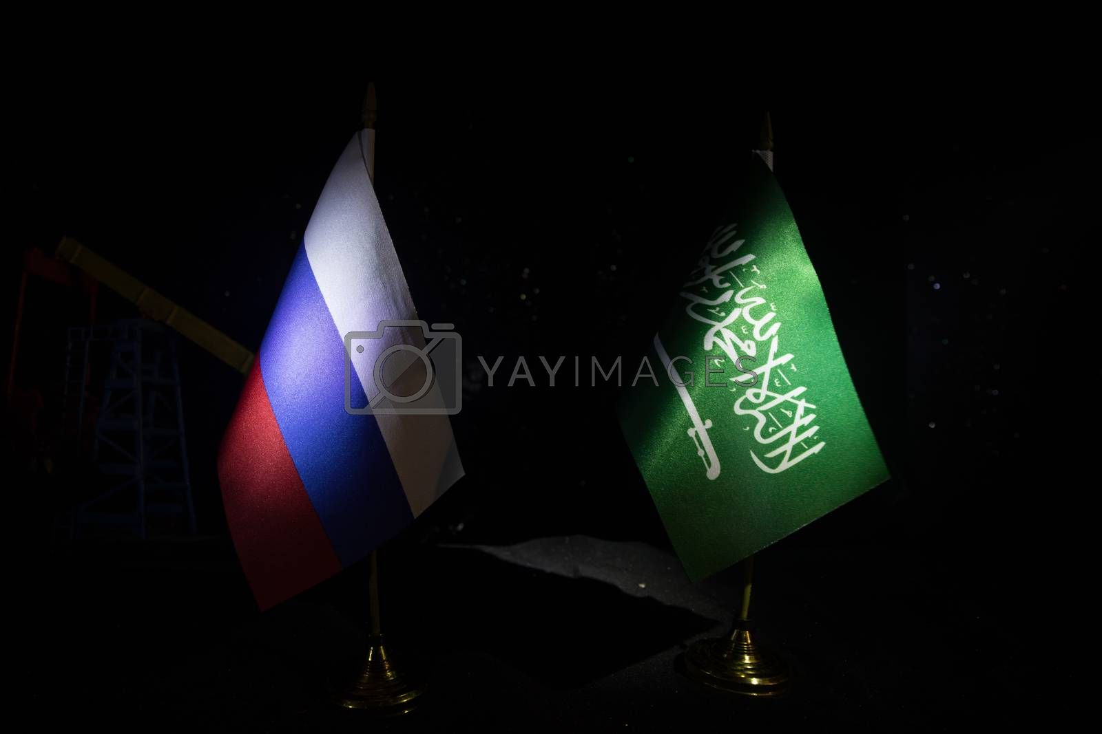 Business dialogue, oil agreement concept: National flags with Oil pump and oil refining factory at night. Energy industrial concept. Selective focus. Artwork decoration.