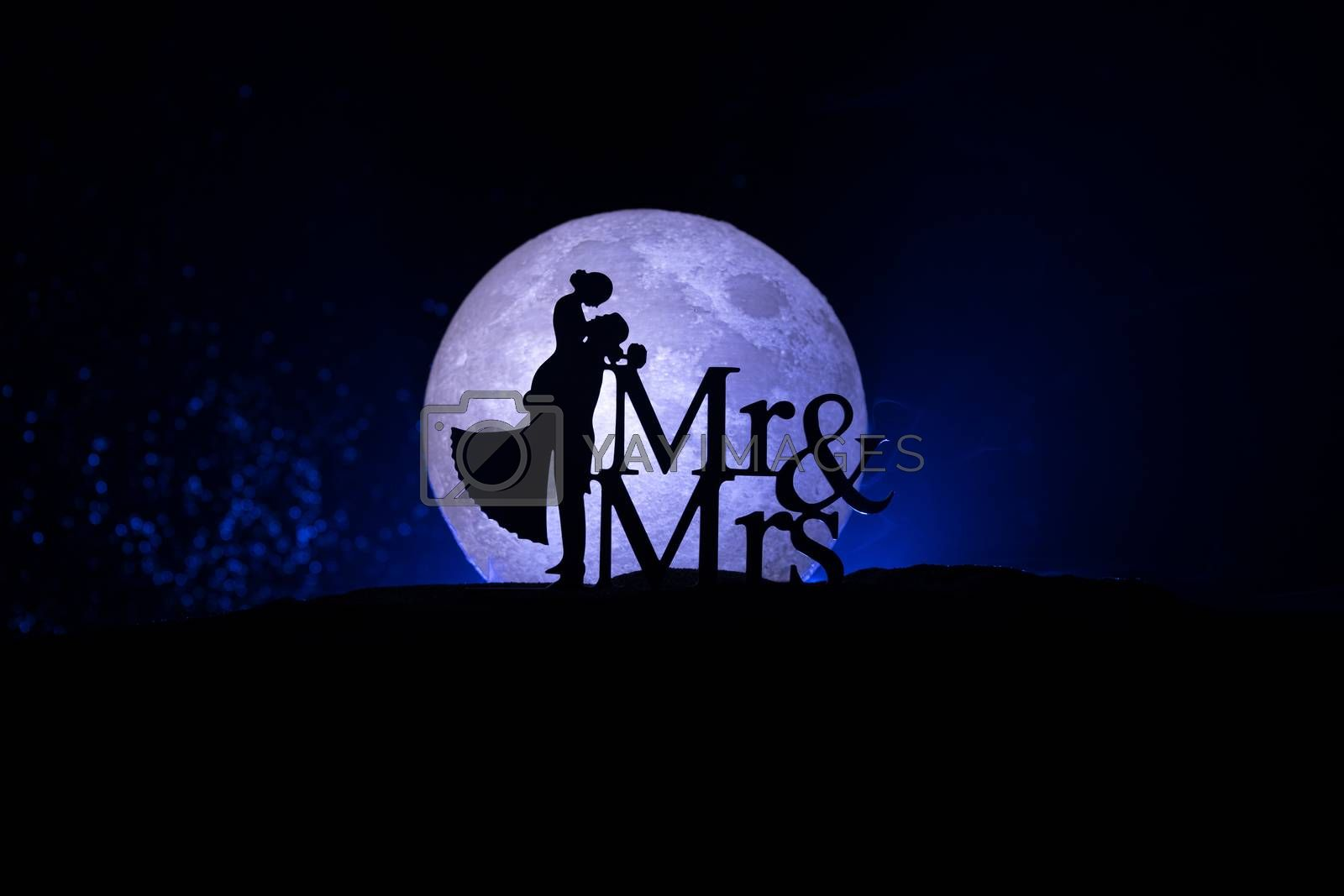Silhouettes of a couple with starry and lunar background. Happy couple at night under moonlight. Creative artwork table decoration.