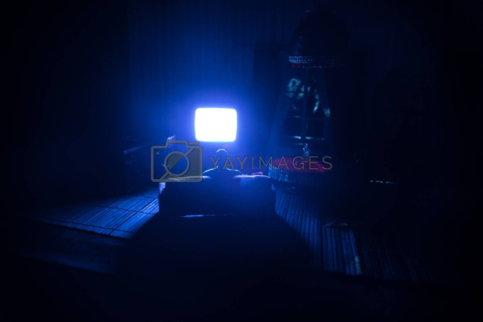 A realistic dollhouse living room with furniture and window at night. Artwork table decoration with handmade realistic dollhouse. Silhouette of a man wathing retro style Television in dark room. Selective focus.