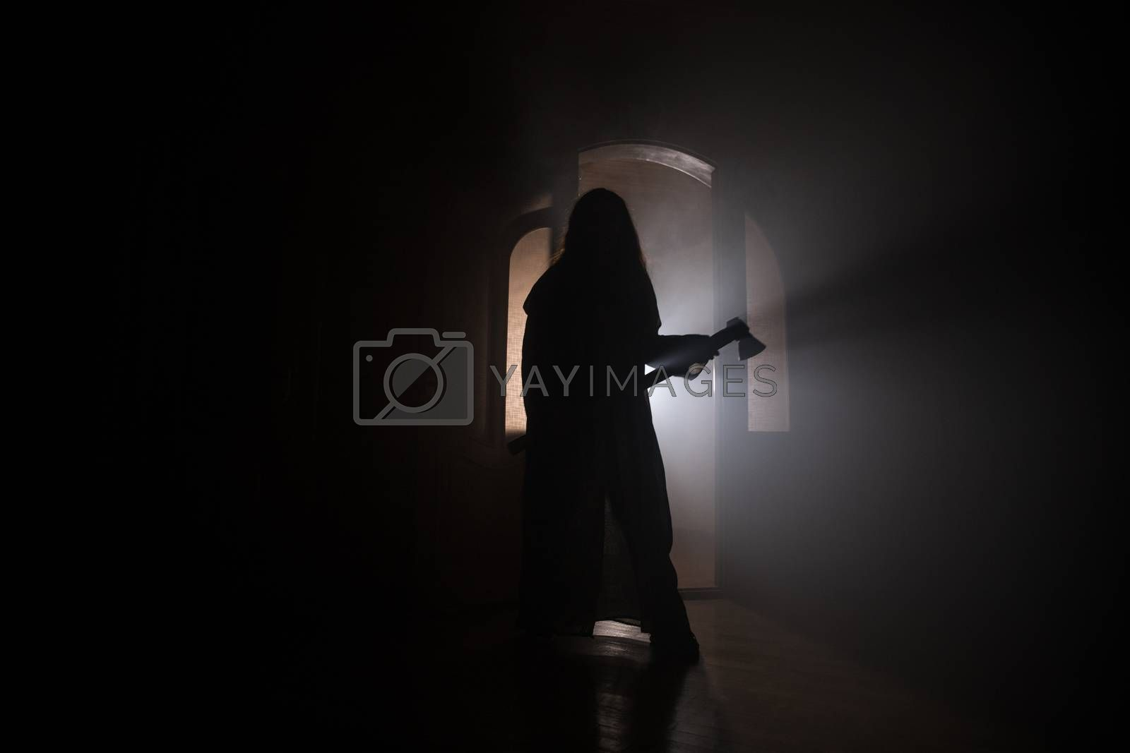Spooky silhouette girl at night with smoke in background. Horror woman holding old axe. Selective focus