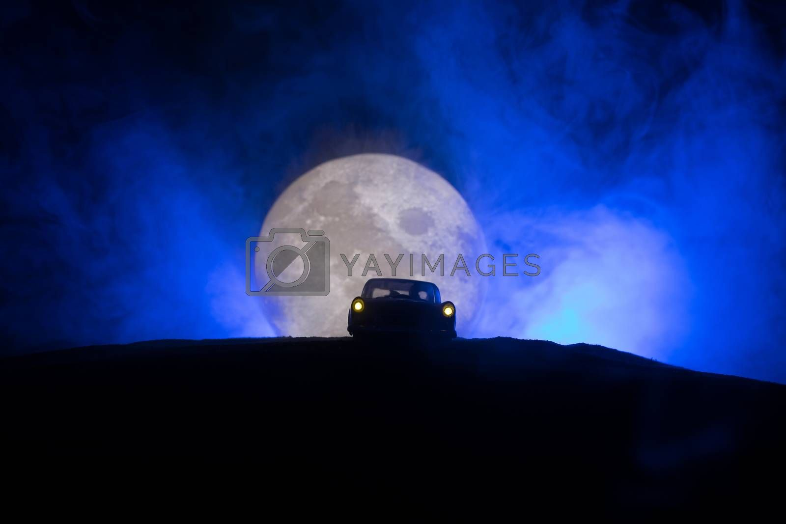 Silhouette of the car and two lovers inside with lunar background. Happy couple at night under moonlight. Creative artwork table decoration.