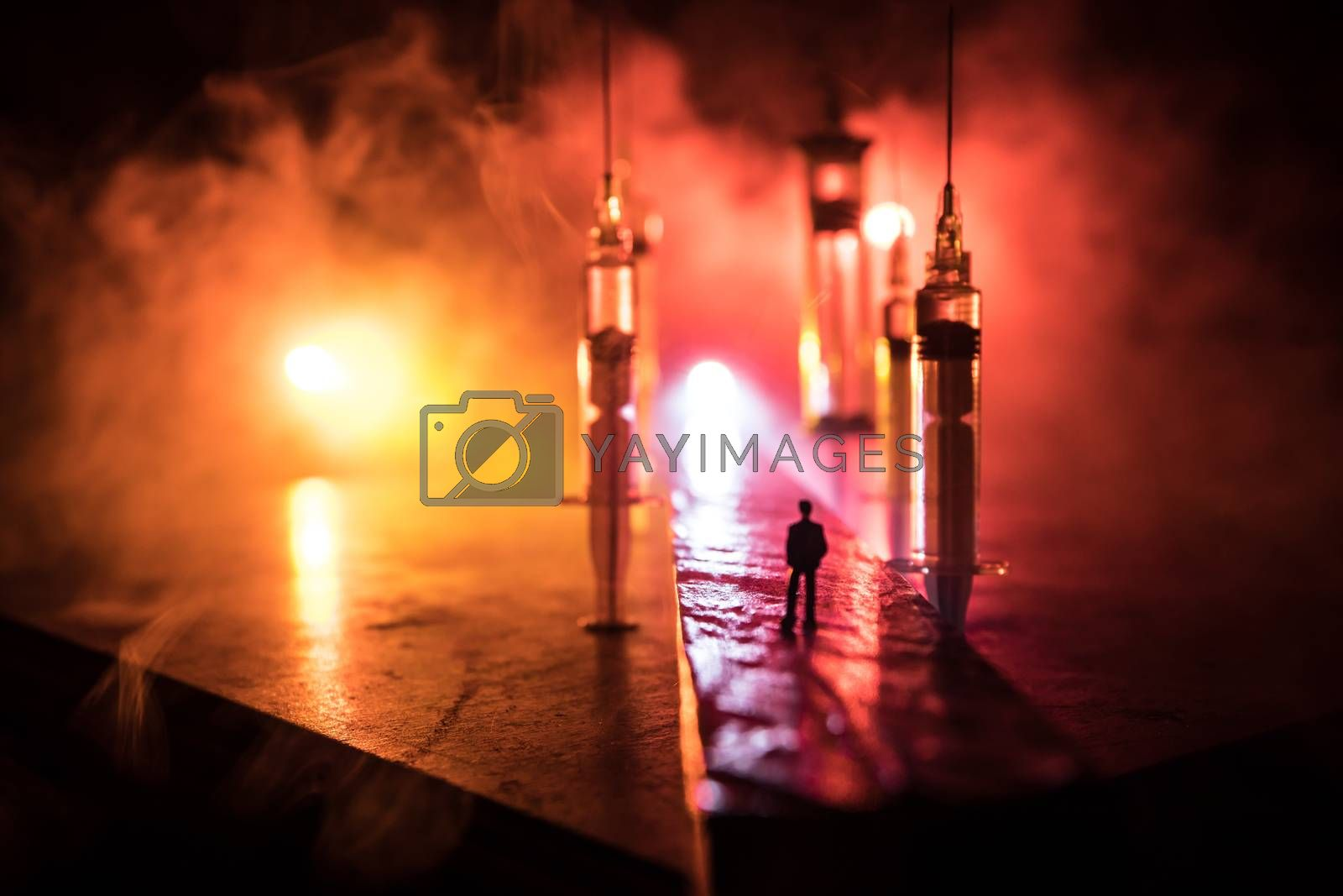 Narcotic drug problem concept. Silhouette of a man standing in the middle of the road on a misty night with giant Drug syringe and narcotic attributes. Creative artwork decoration