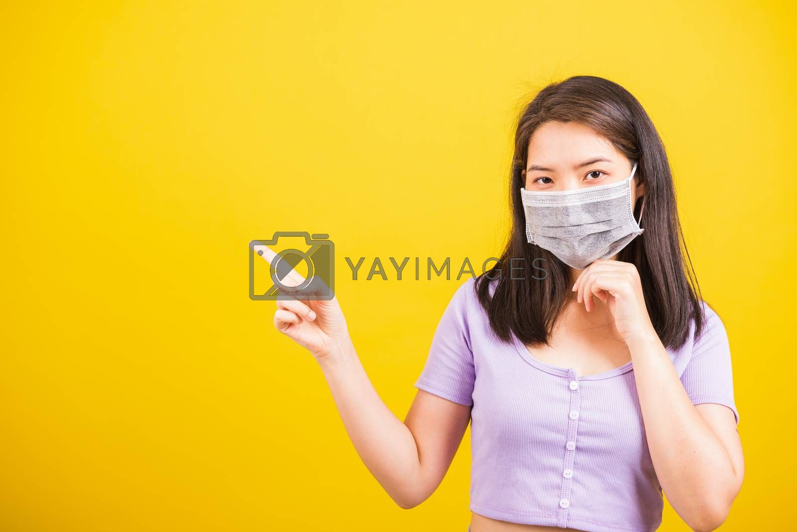 Asian young teen woman wearing face mask protective against coronavirus or COVID-19 virus or filter dust, air pollution her point finger to side space, studio shot isolated yellow background