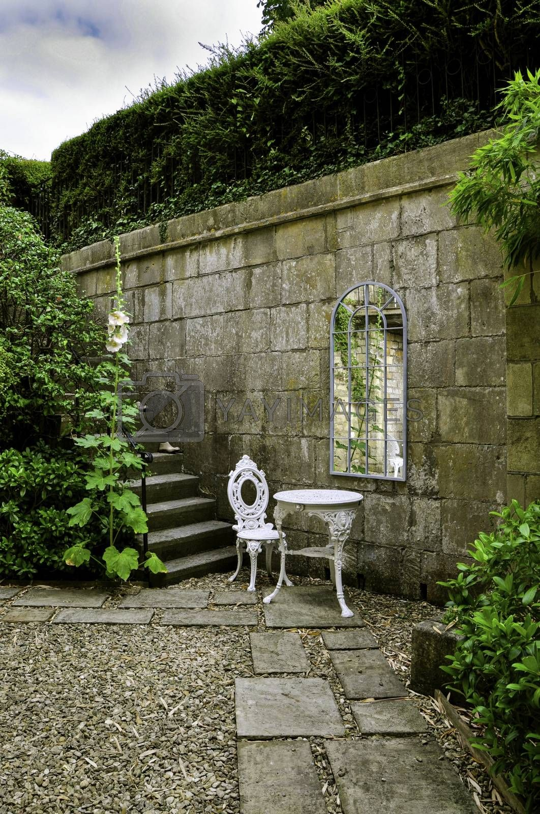A stone walled cottage garden with steps, shrubs and hollyhocks. The wall is decorated with a Georgian mirror infront of an ornate white wrought iron table and chair set of garden furniture.