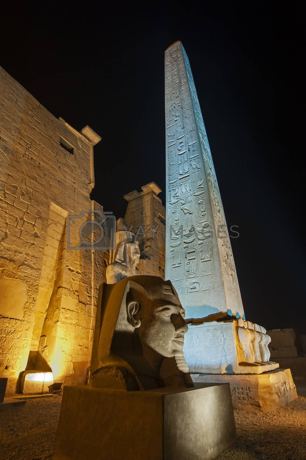 Large statue and obelisk at entrance pylon to ancient egyptian Luxor Temple lit up during night