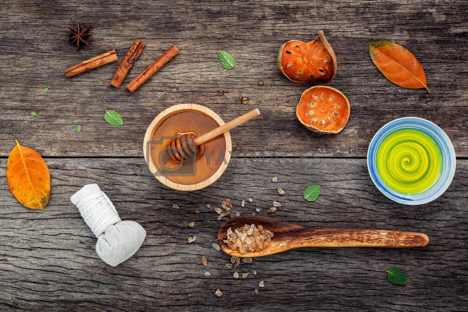 Composition of nature spa ingredients on the dark wooden table. Spa and wellness with dried indian bael ,herbal compress ball,turmeric,cinnamon powder ,cinnamon sticks ,aromatic oil and star anise.