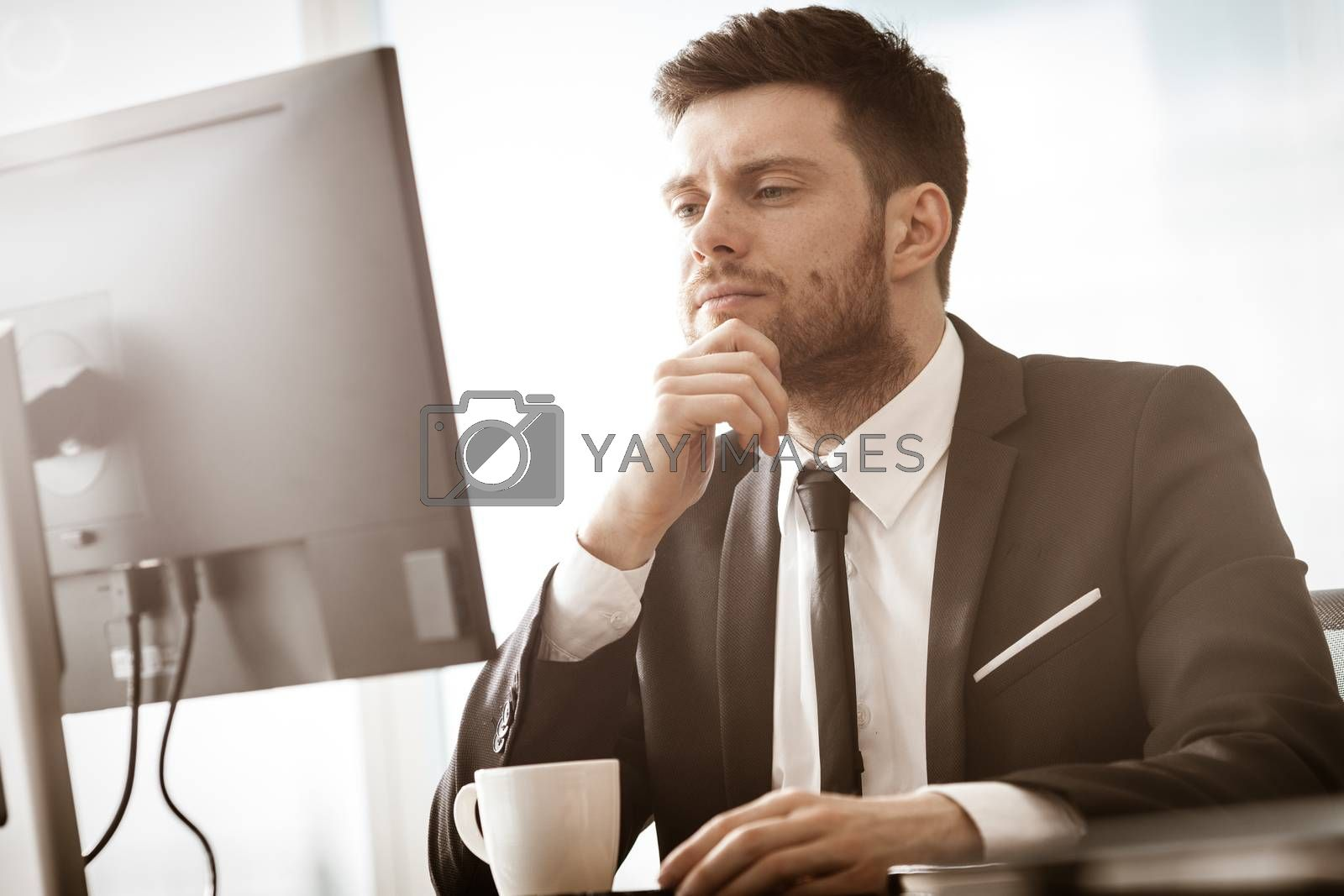 Business crisis concept. Young businessman sitting at the office table busy talking on a cell phone resolving a very serious work problem. Man in suit indoors on glass window background by mtoome