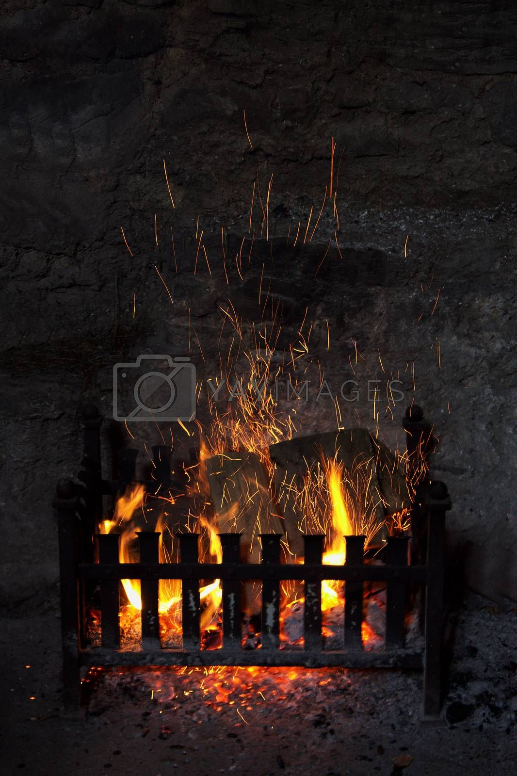 Old fashioned open log fireplace in with flames and sparks