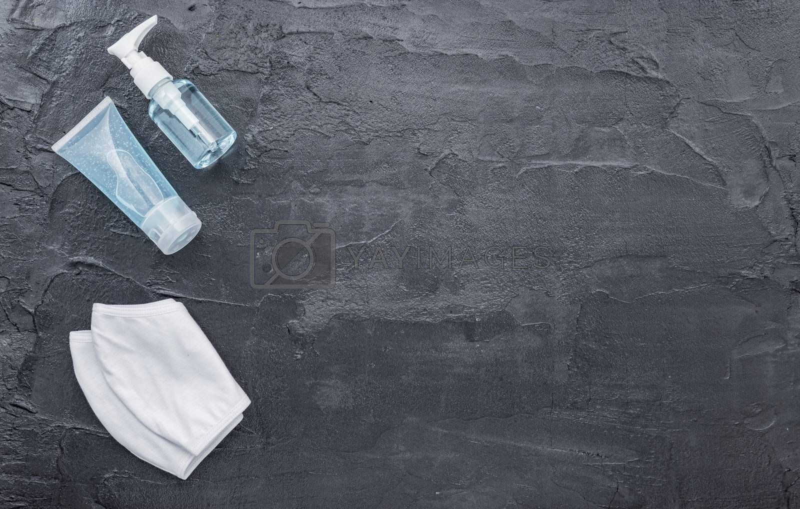 Survival kit disposable mask and alcohol gel against Coronavirus Disease 2019 COVID 19  on dark black concrete wall texture background.
