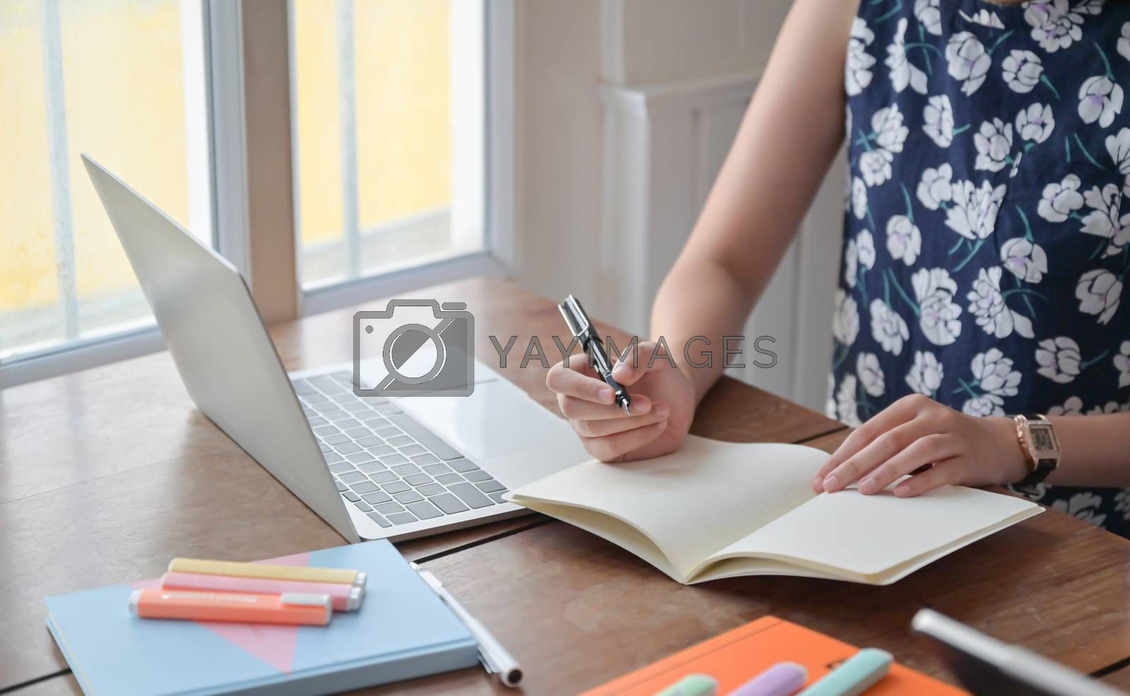 Royalty free image of Young woman recording online meetings at her home,work from home by poungsaed